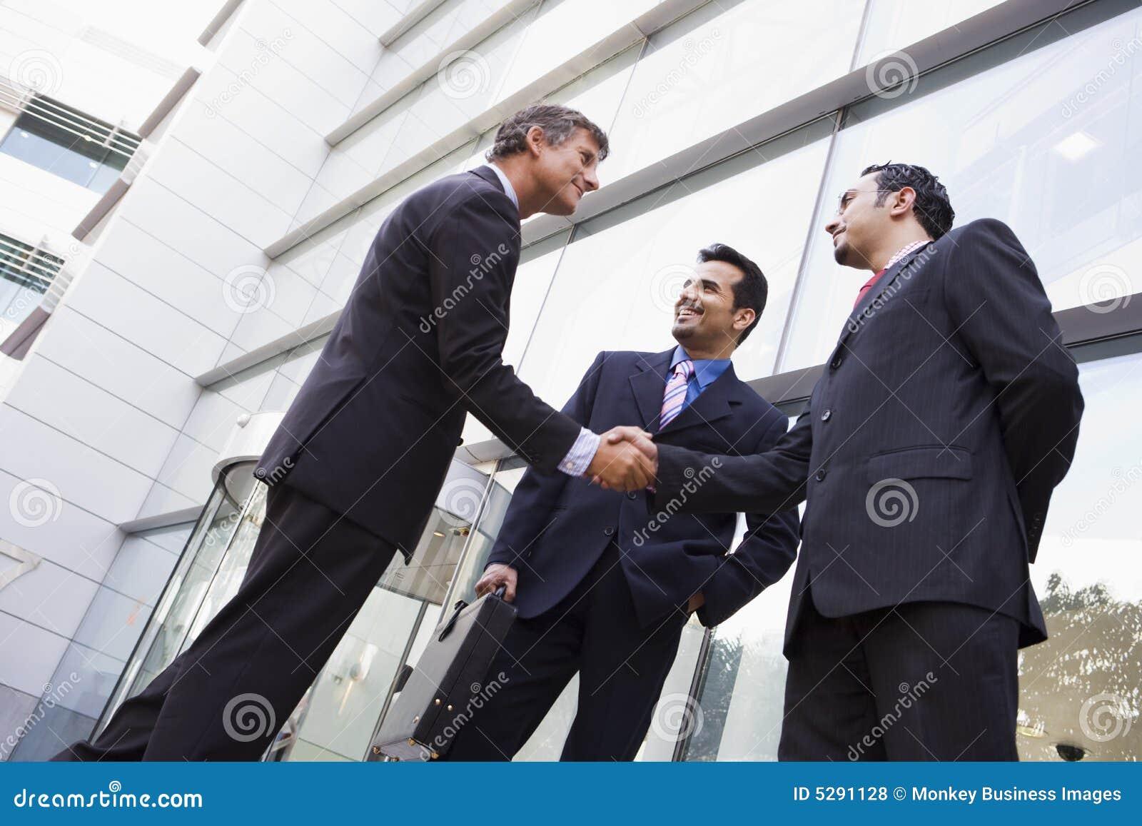 Geschäftsleute, die Hände außerhalb des Büros rütteln