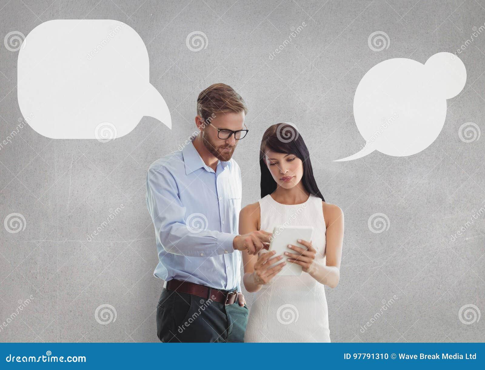 Geschäftsleute mit Rede sprudeln, eine Tablette betrachtend gegen grauen Hintergrund