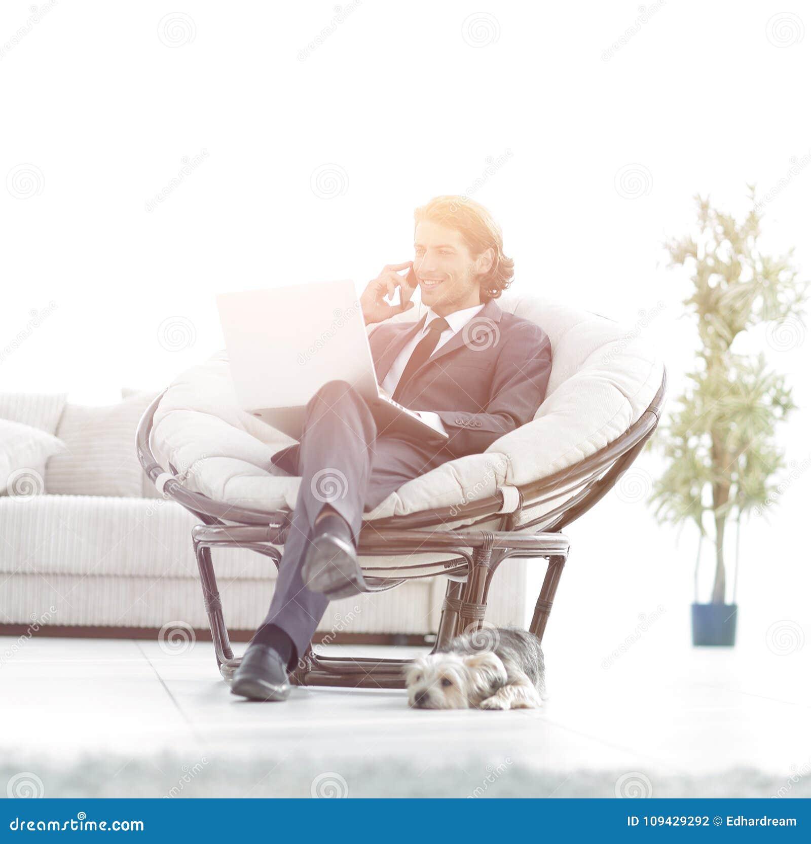 Geschäftsmann, der auf einem Smartphone sitzt im Wohnzimmer spricht