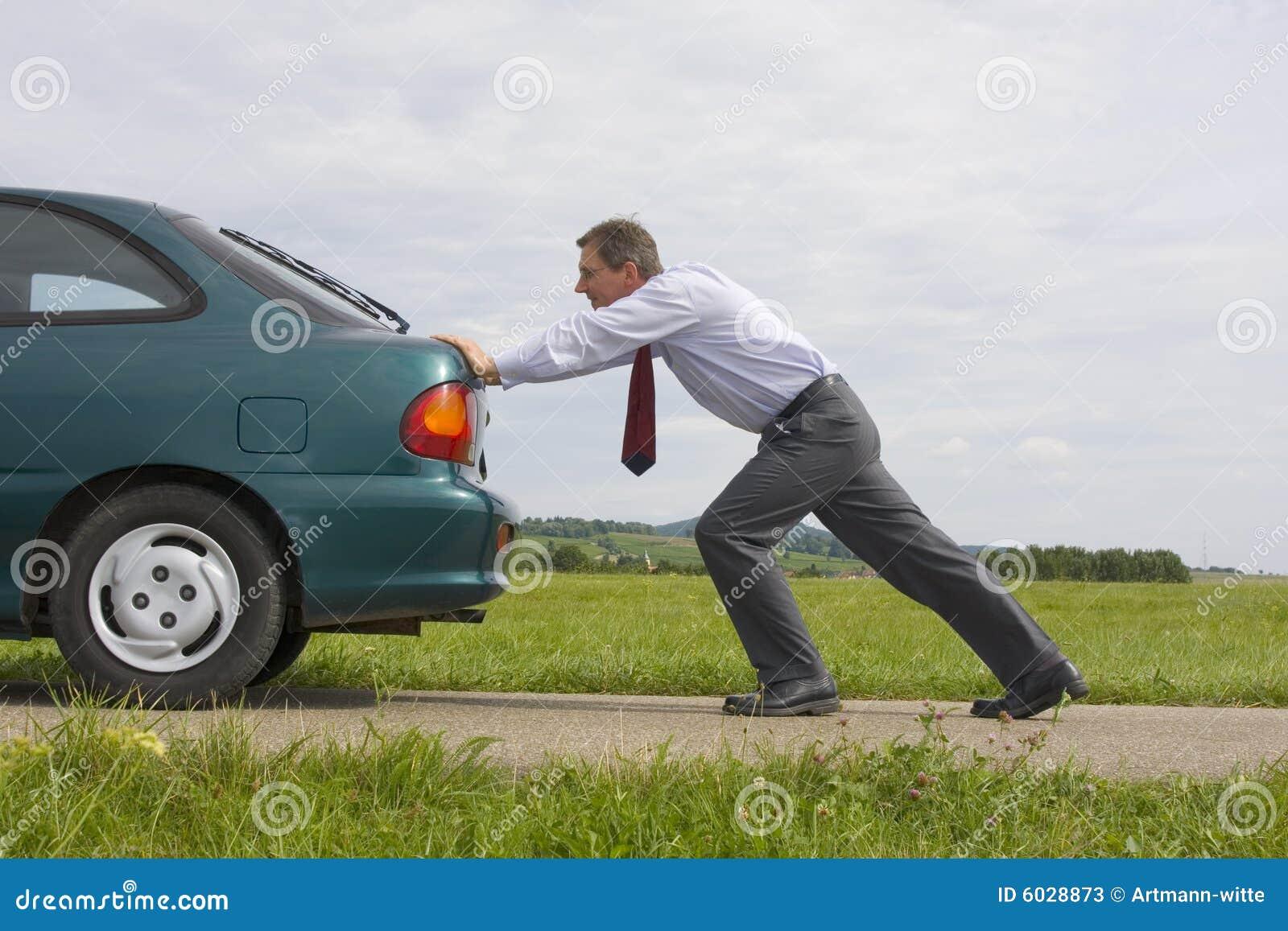 Geschäftsmann, der ein Auto drückt