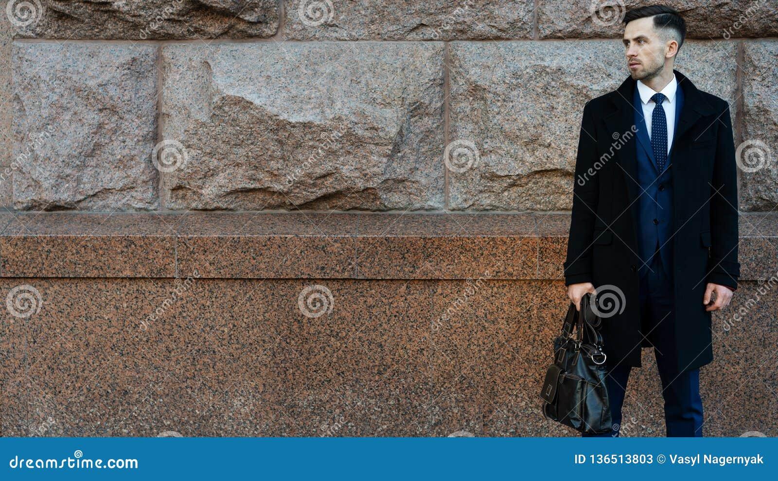 Geschäftsmann, der einen Aktenkoffer nahe der Wand hält Suchen Sie nach Hintergrund