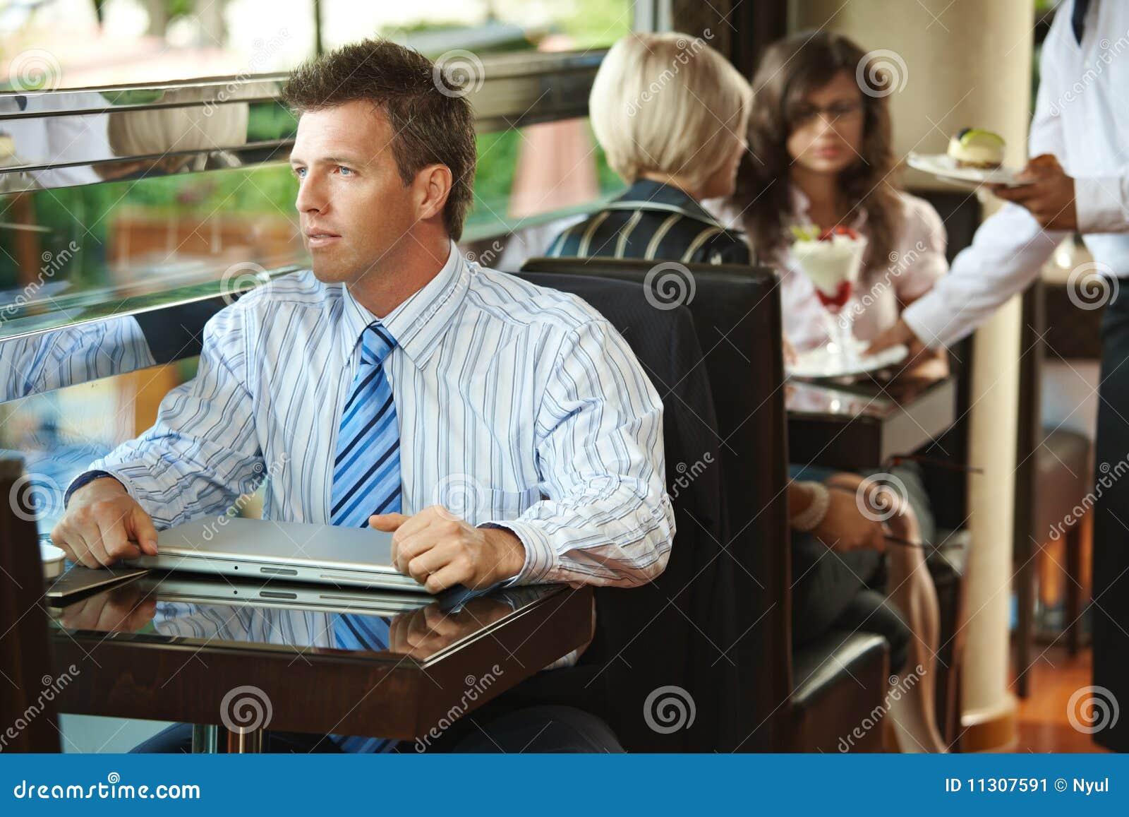 Geschäftsmann, der im Kaffee sitzt