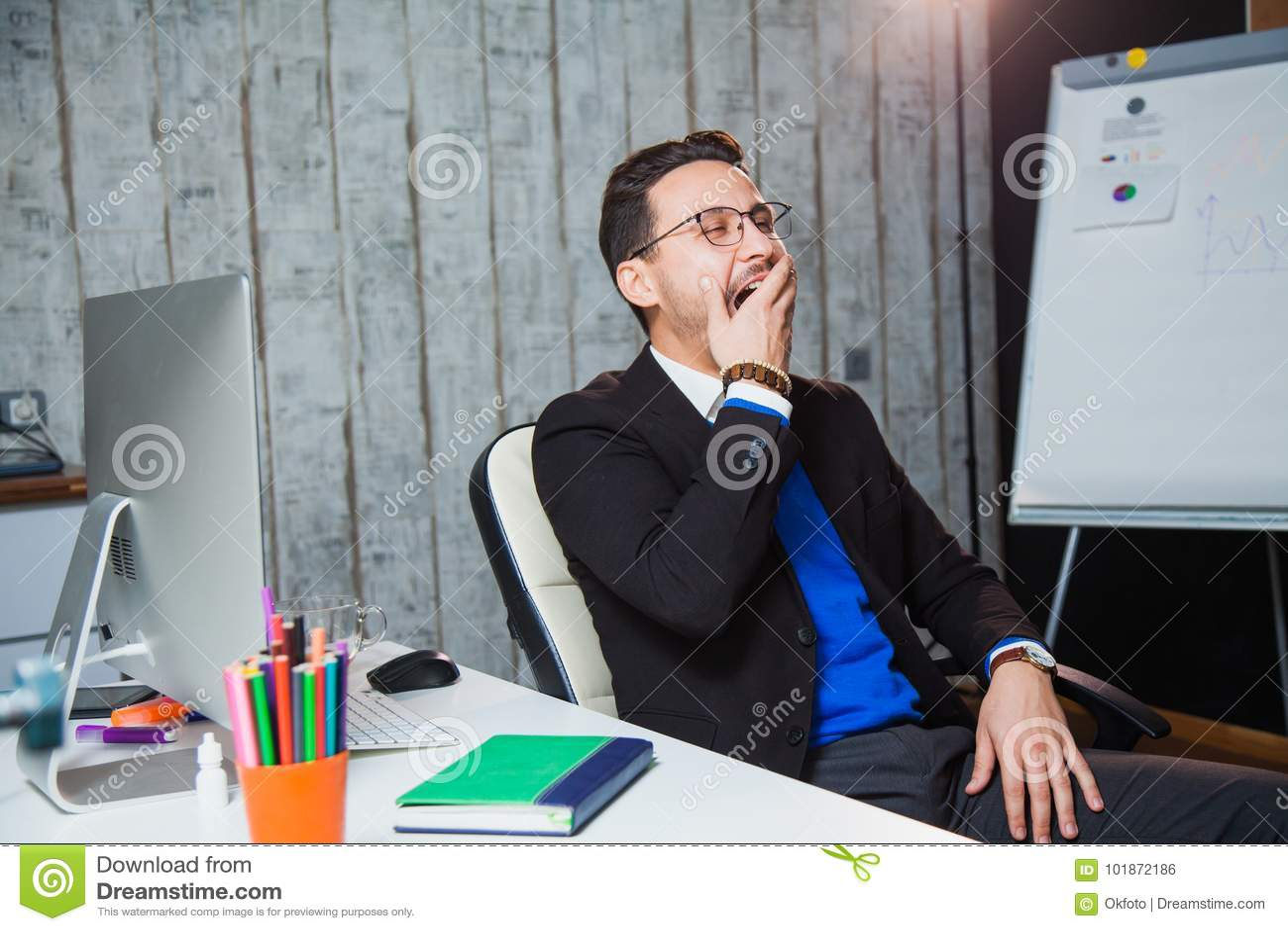 Geschäftsmann, der an langweiligem Jobkonzept des Büros gähnt