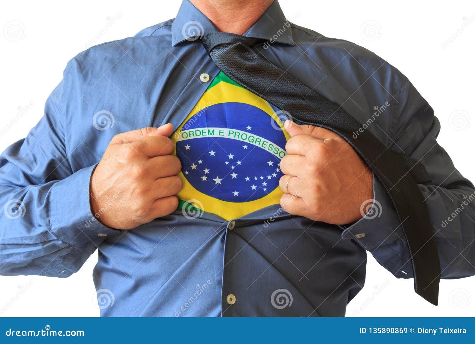 Geschäftsmann, der sein T-Shirt offen, Brasilien-Staatsflagge zeigend zieht Weißer Hintergrund