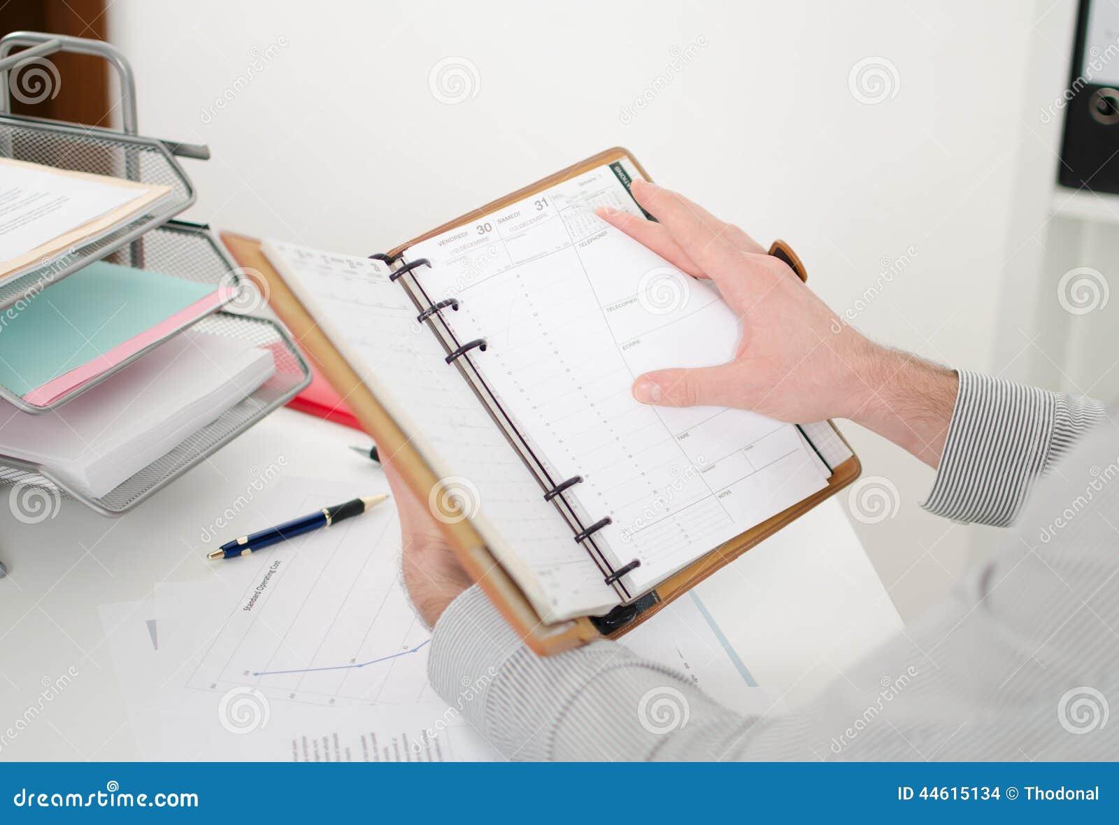Geschäftsmann, der seine Tagesordnung konsultiert