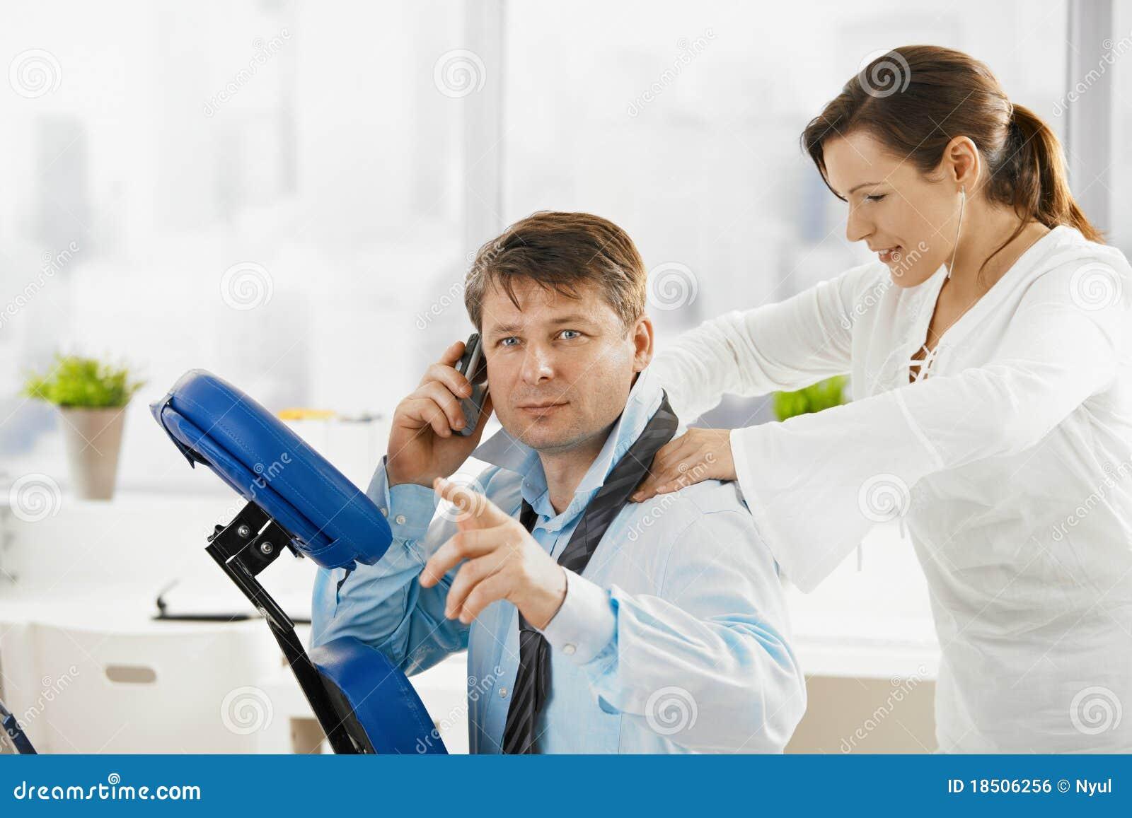 Geschäftsmann, der am Telefon während der Massage spricht