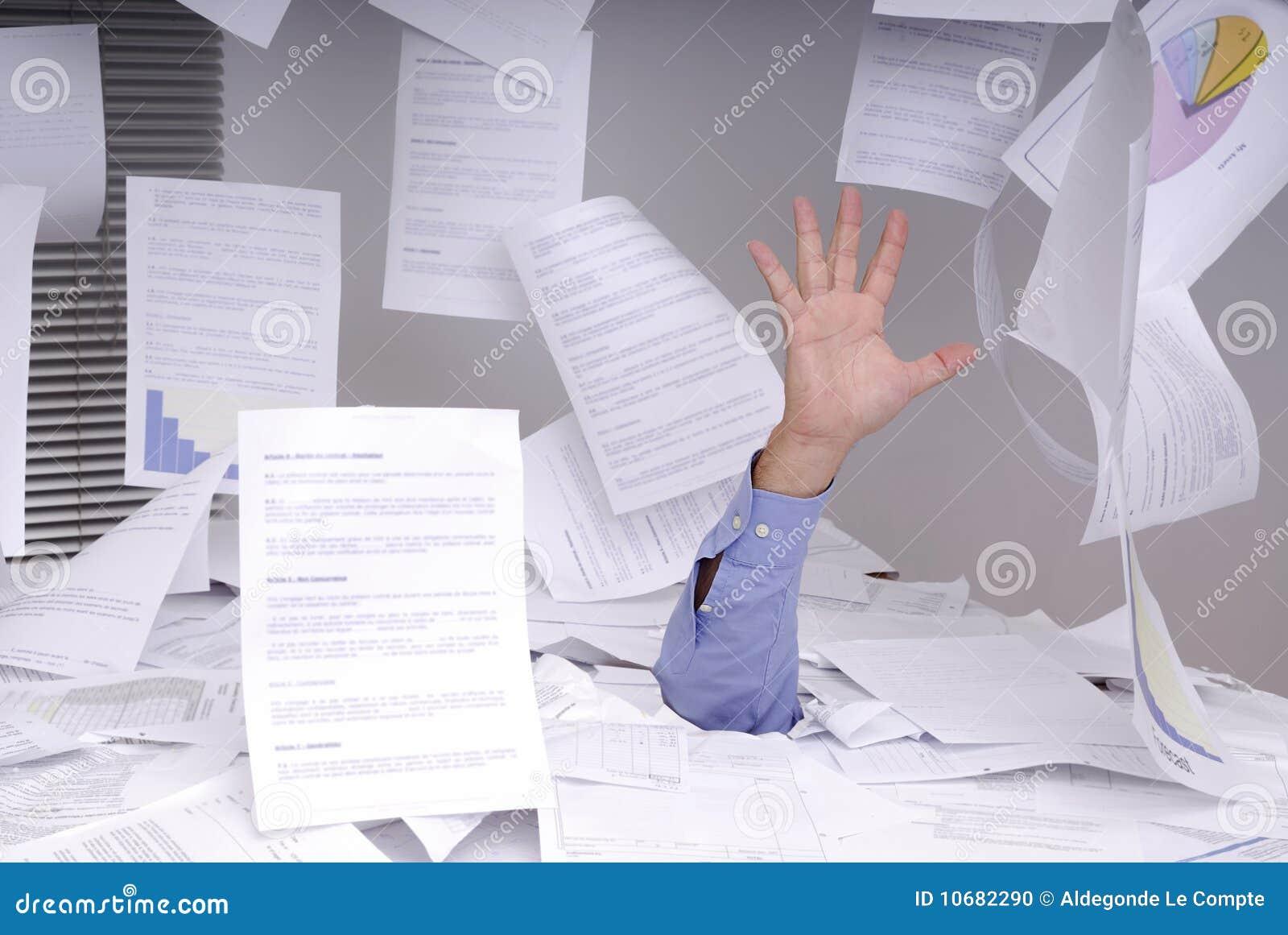 Geschäftsmann, der voll in einem Schreibtisch der Papiere ertrinkt
