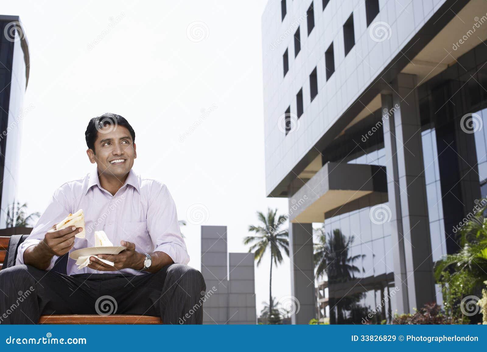 Geschäftsmann-Eating Sandwiches Outside-Bürogebäude