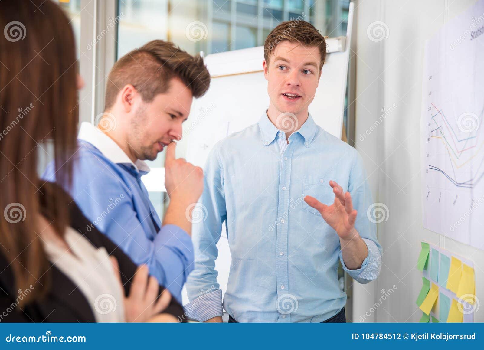 Geschäftsmann Gesturing While Communicating mit Kollegen