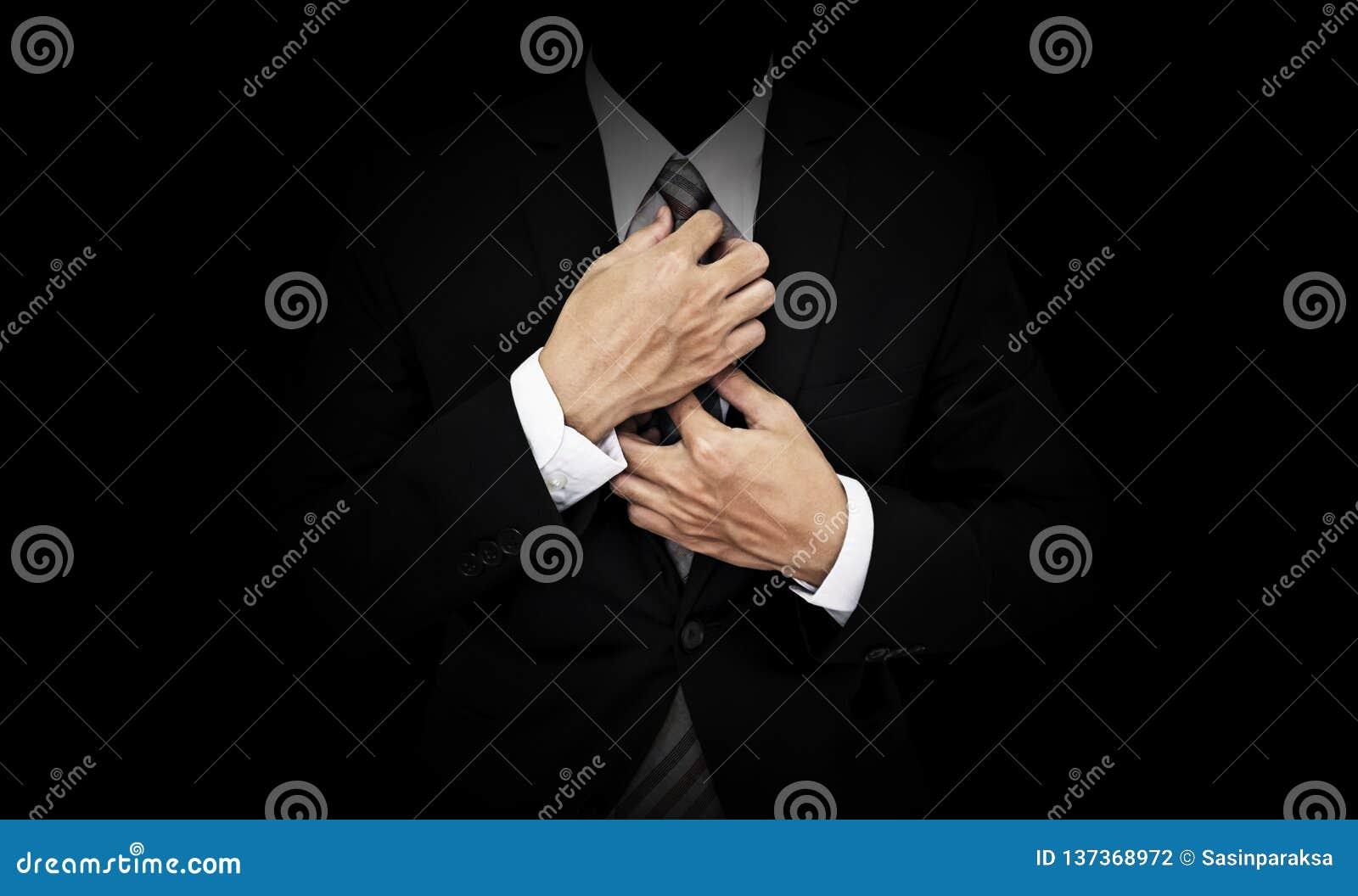 Geschäftsmann im schwarzen Anzug, der Krawatte, auf weißem Hintergrund bindet