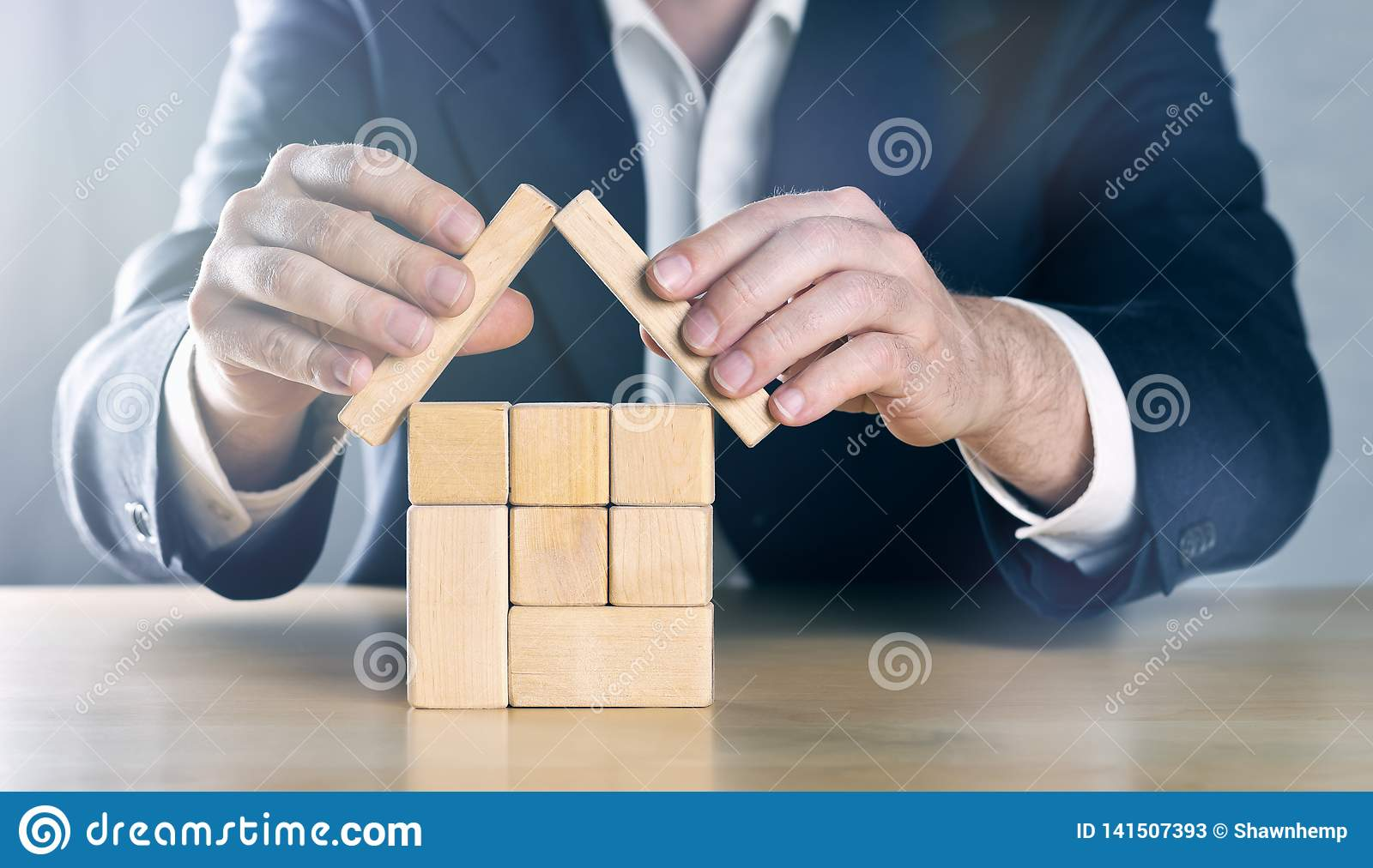 Geschäftsmann, Immobilienagentur, Versicherungsagent oder Architekt, die schützendes Dach über dem Haus gemacht von hölzernem ver
