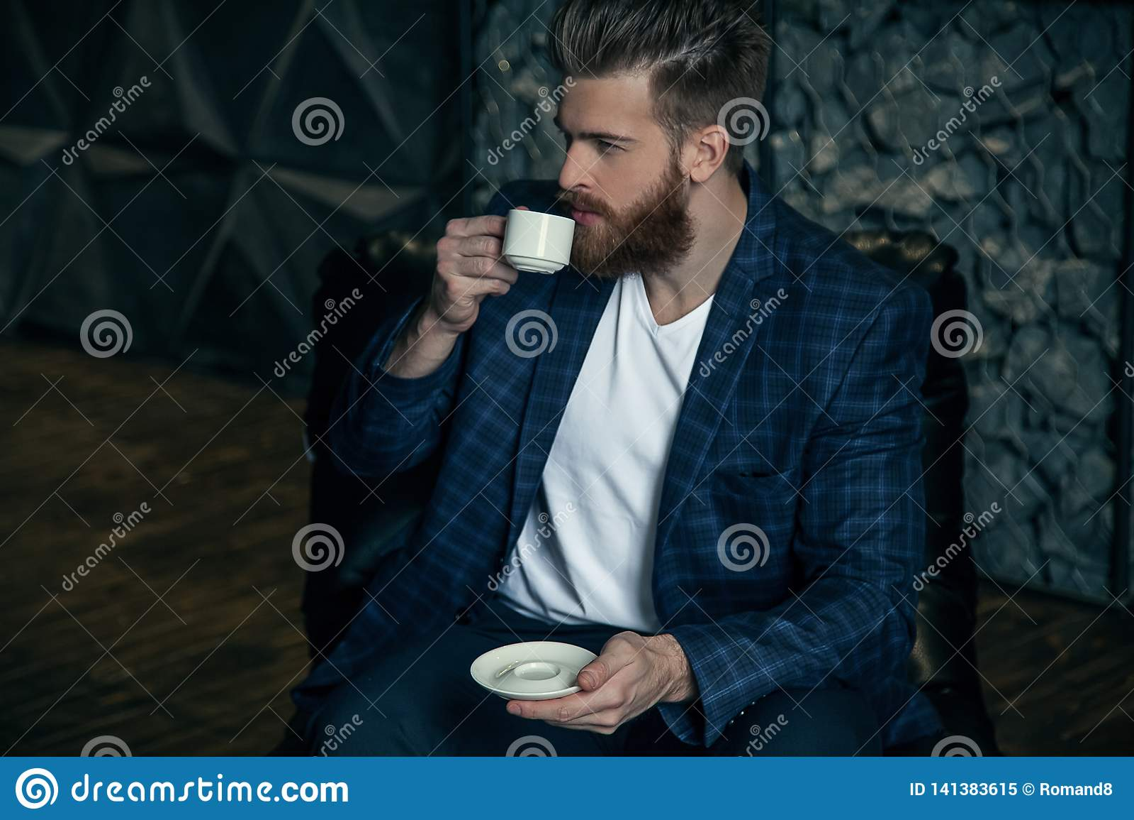 Geschäftsmann mit dem Tasse Kaffee, der gegen modernen Hintergrund stationiert