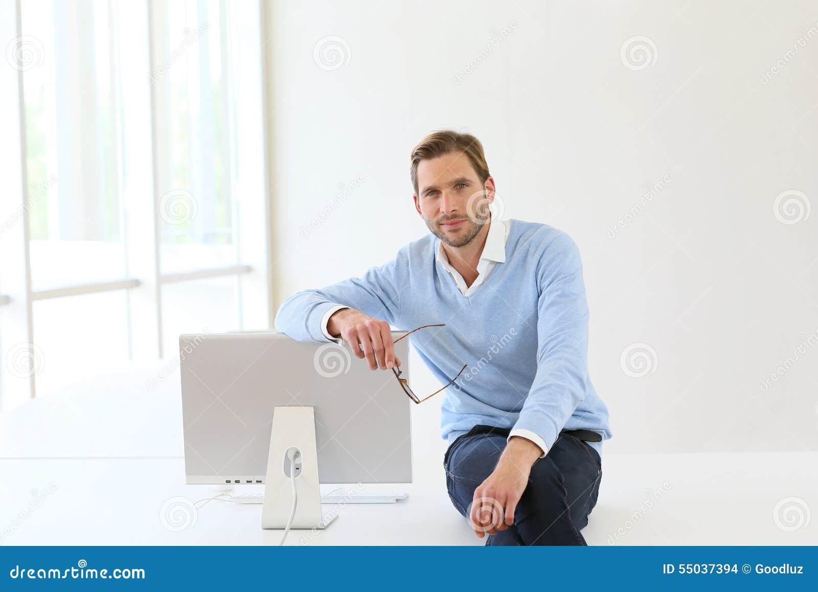 Geschäftsmann Sitting On Desk