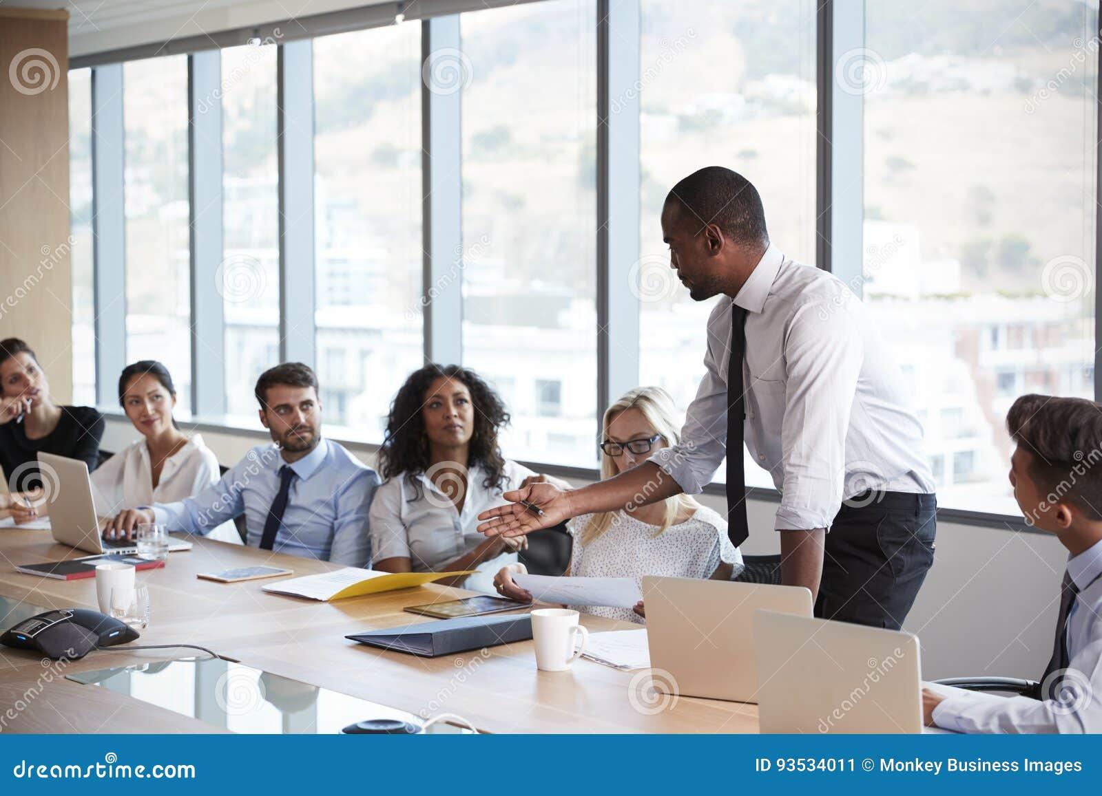 Geschäftsmann-Stands To Address-Sitzung um Brett-Tabelle
