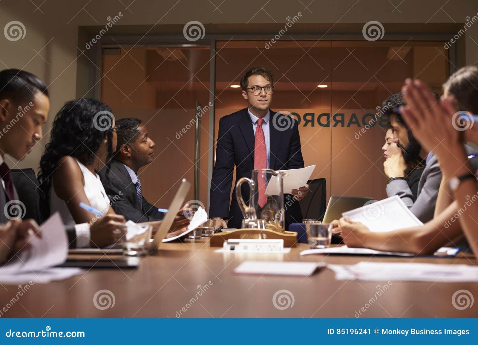 Geschäftsmann steht, sprechend zu Team bei der Sitzung, niedriger Winkel