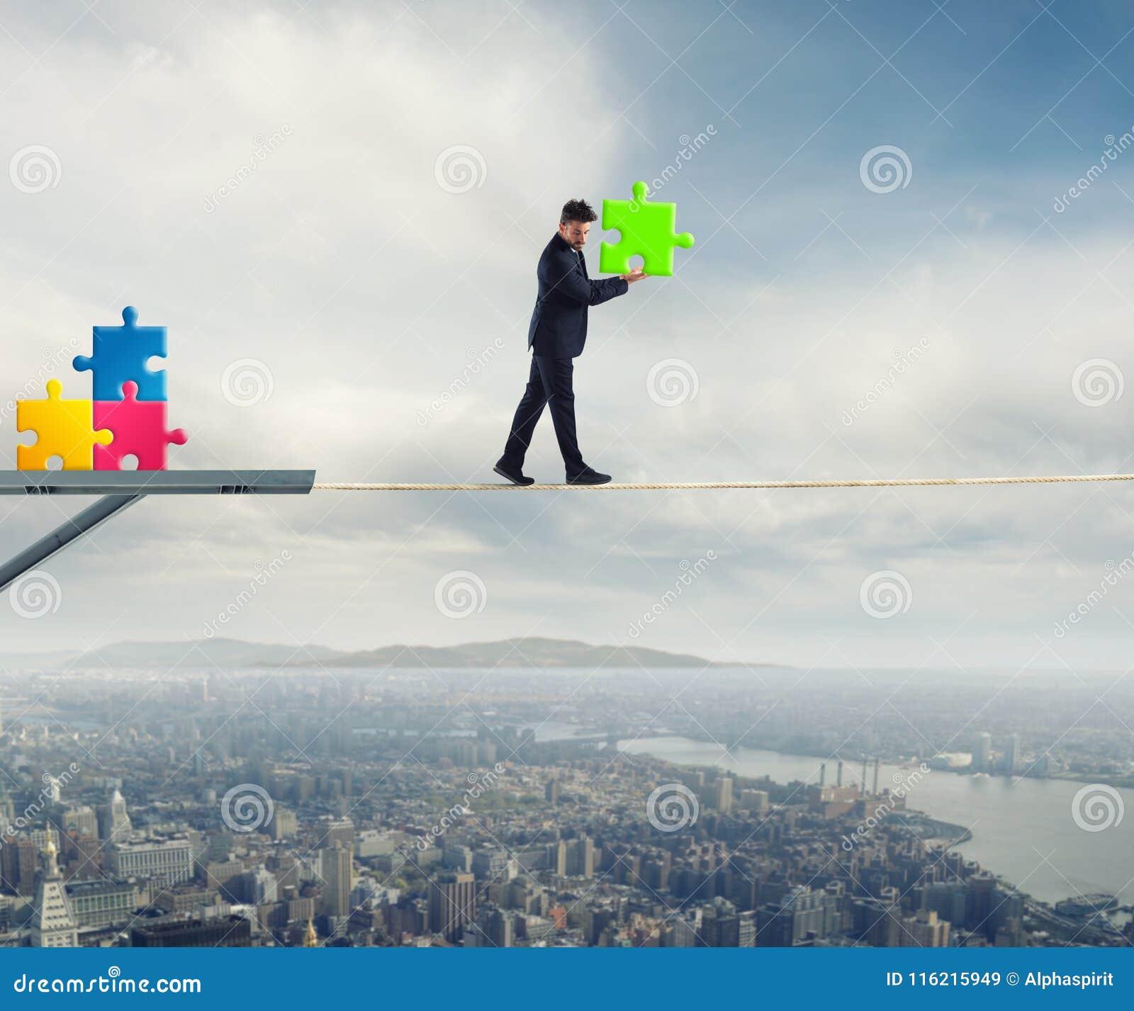 Geschäftsmann trägt ein Stück des Puzzlespiels während er gehend auf ein Seil Konzept des fehlenden Stückes