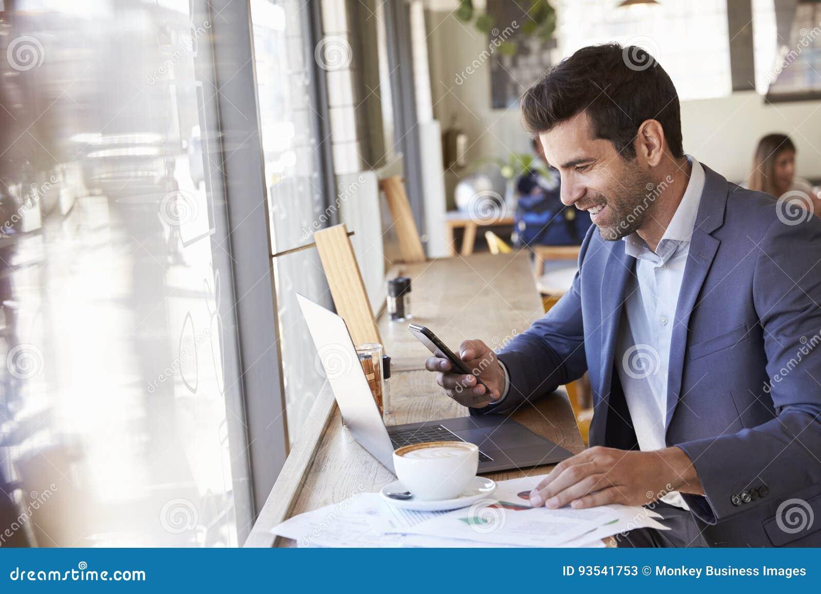 Geschäftsmann Using Phone Whilst, das in der Kaffeestube arbeitet
