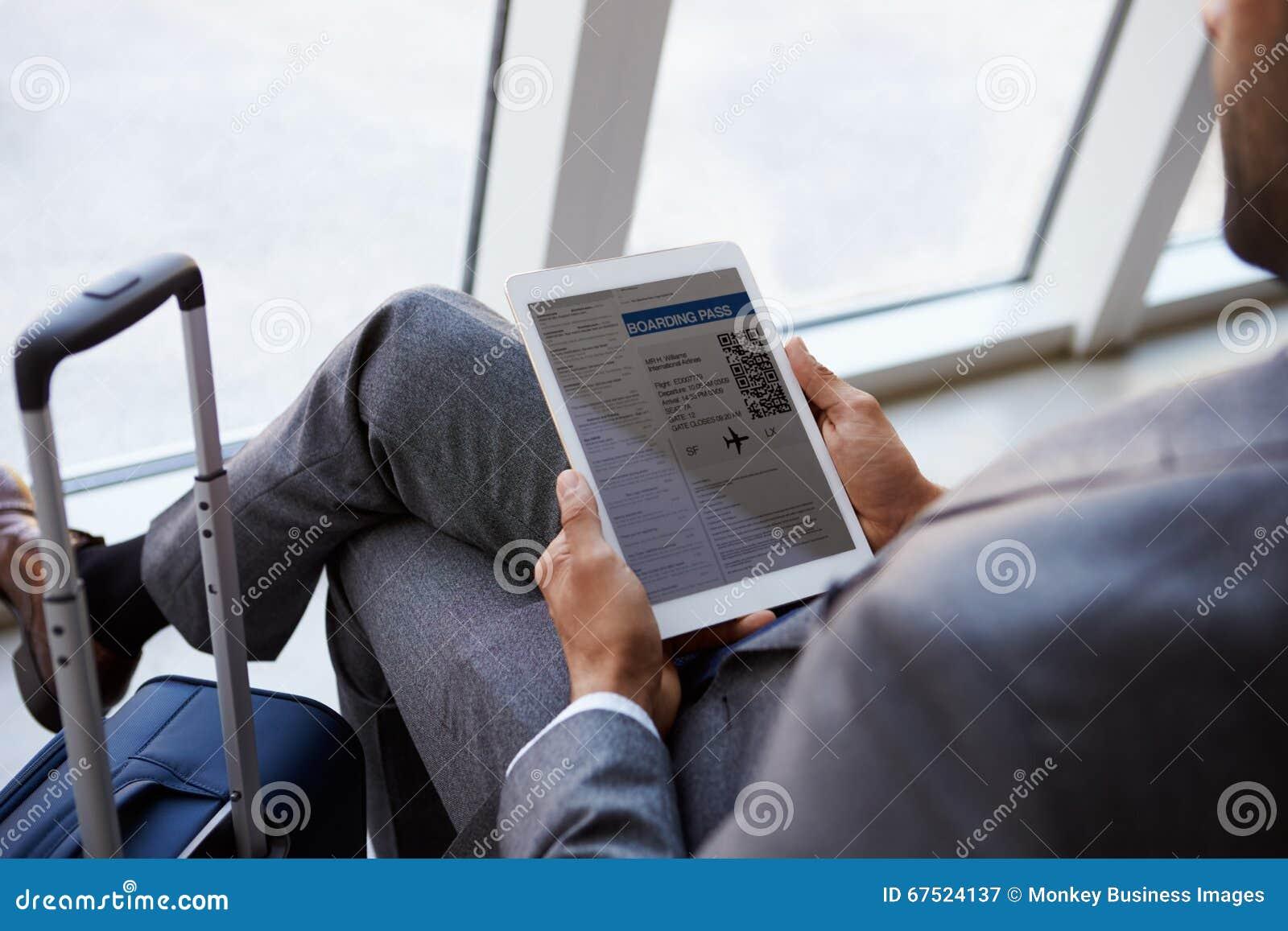 Geschäftsmann Viewing Boarding Pass im Flughafen-Aufenthaltsraum