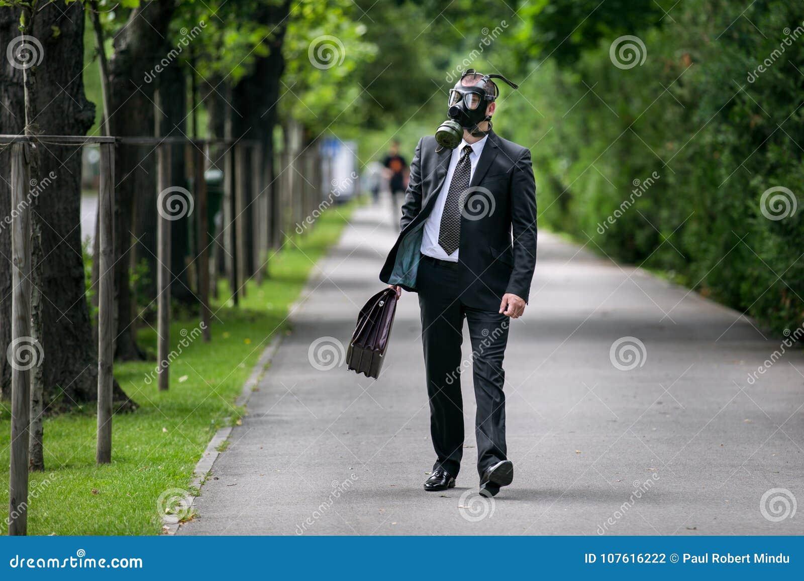 Geschäftsmanngehen im Freien mit dem Aktenkoffer, der eine Gasmaske trägt