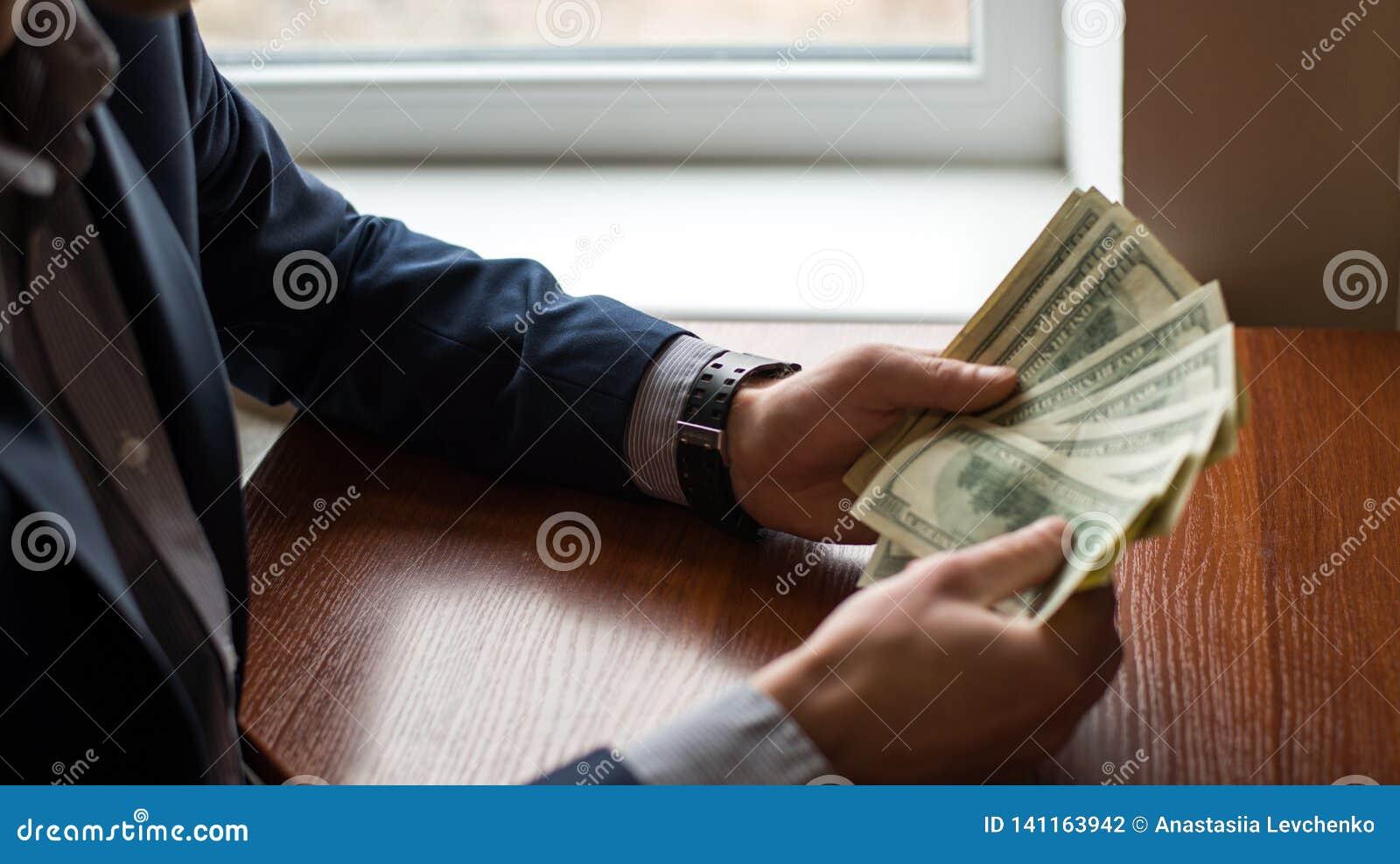 Geschäftsmannhand-Ergreifungsgeld, US-Dollar USD-Rechnungen Mann in der Klage Hölzerner Hintergrund