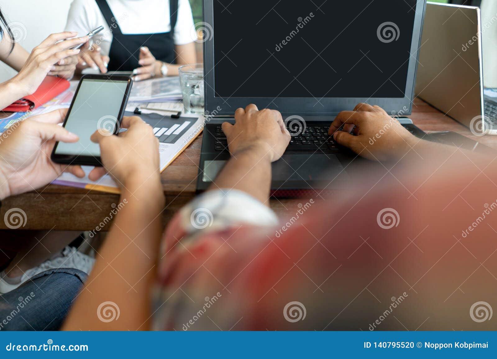 Geschäftsunternehmensleute, die mit intelligentem Telefon- und Laptop-Computer Displaytechnologiemodell auf Schreibtischtabelle a