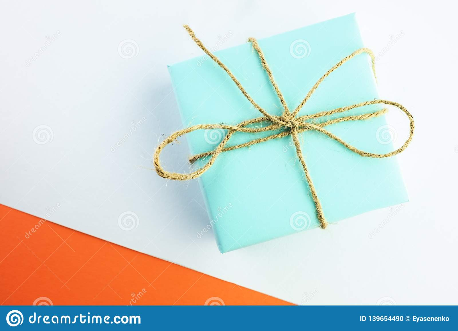 Geschenk der blauen Farbe gebunden mit Schnur auf einem weiß-orange Hintergrund