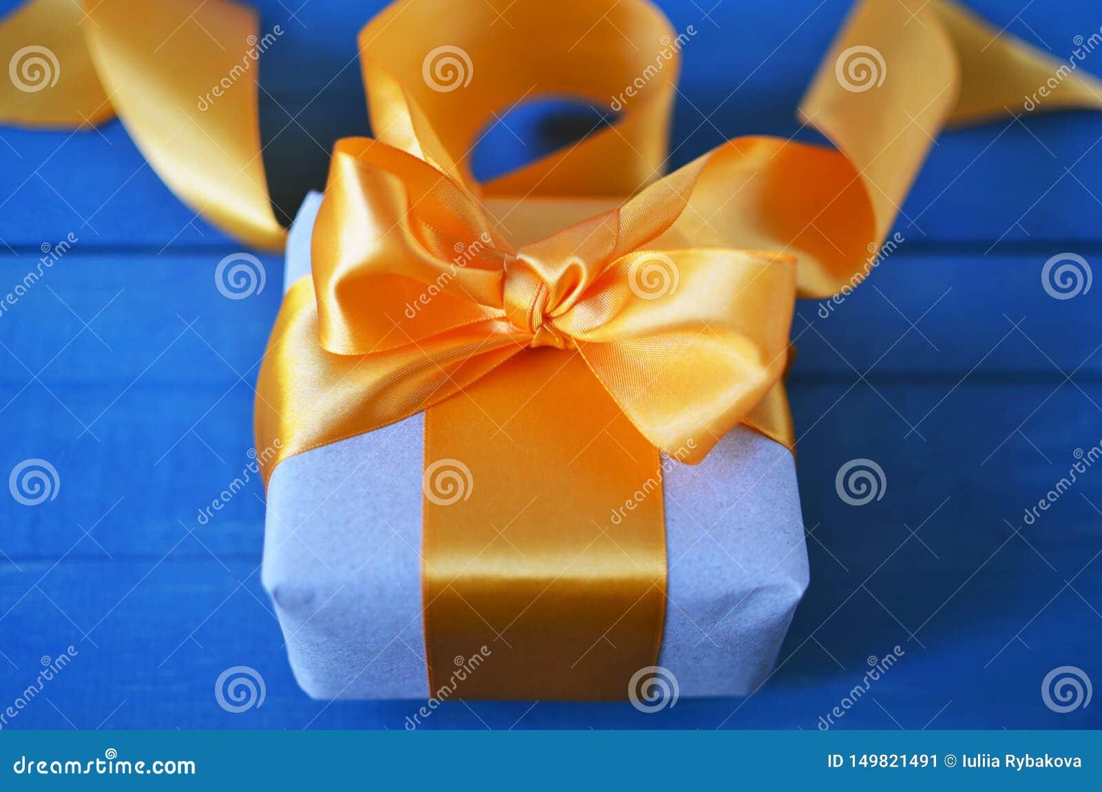 Geschenkbox eingewickelt mit Kraftpapier und Bogen auf neutralem Hintergrund mit boke Gl?cklicher Mann genie?t an den Feiertagen