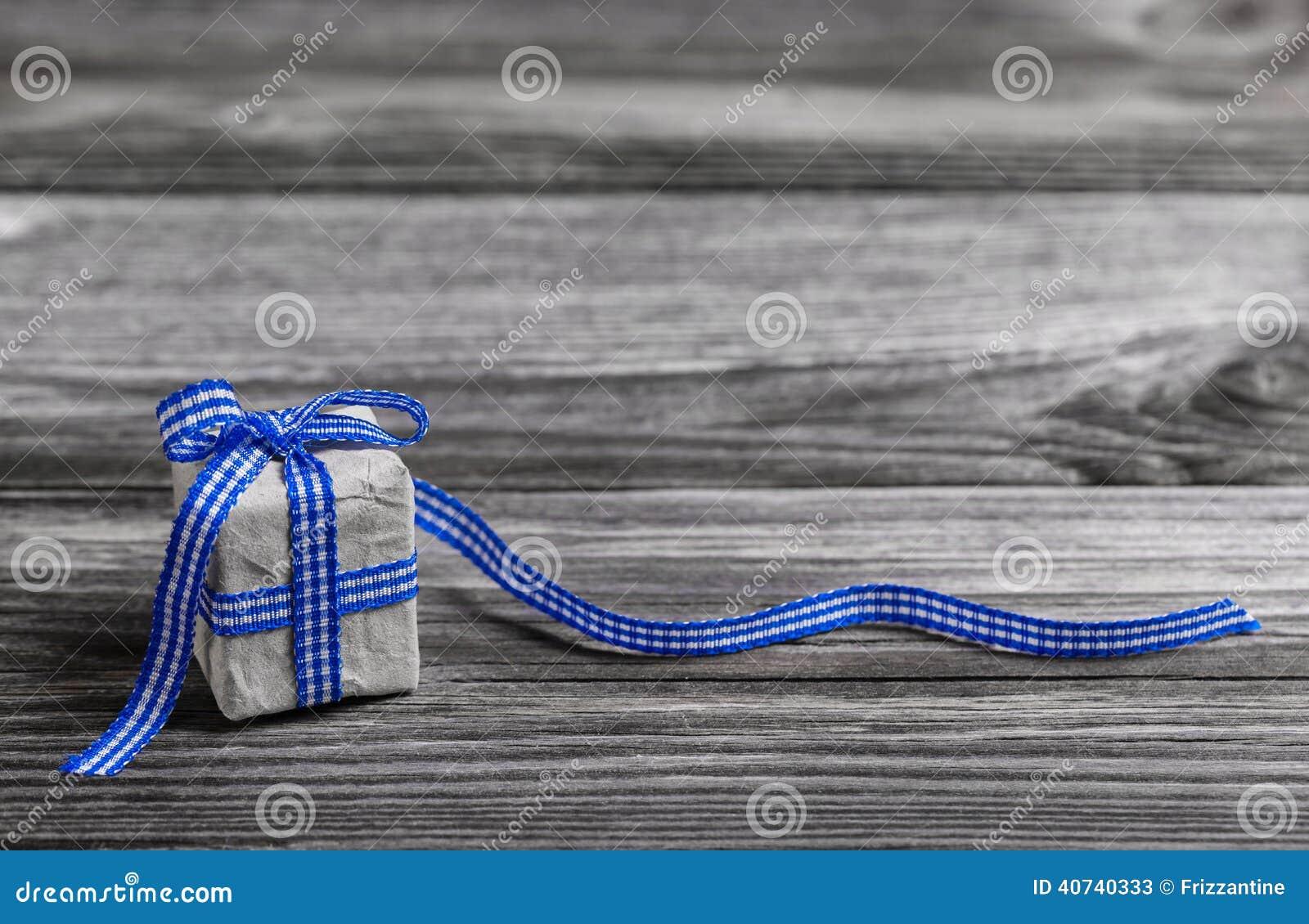 Geschenkbox mit Blau überprüfte Band auf hölzernem grauem Hintergrund