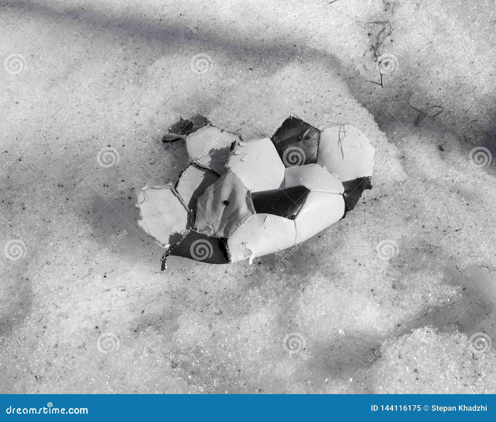 Gescheurde bal voor het spelen van voetbal die op de sneeuw liggen