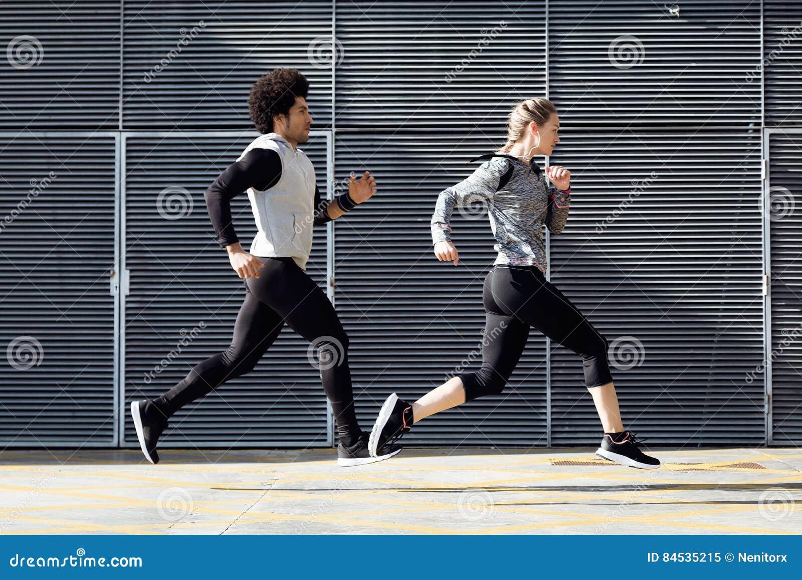 Geschikt en sportief paar die in de straat lopen
