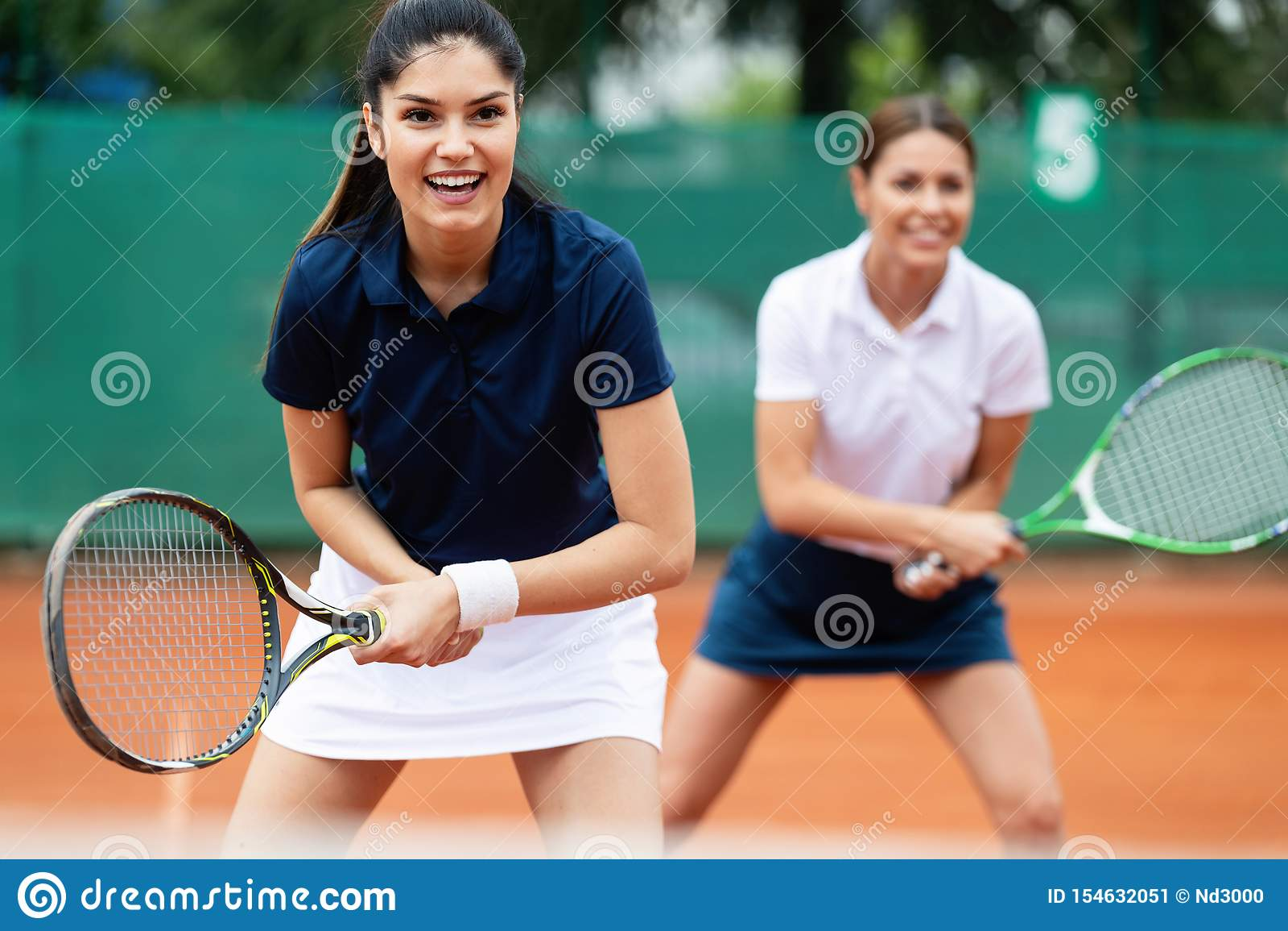 Geschikte gelukkige mensen die tennis samen spelen Het concept van de sport
