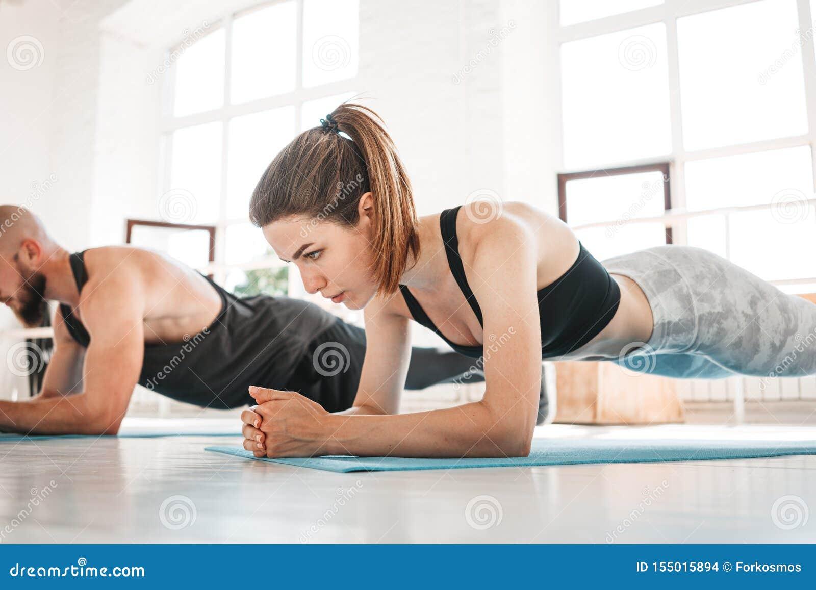 Geschikte jonge vrouw en man werkende abs die in witte binnenlandse gymnastiek uitoefenen