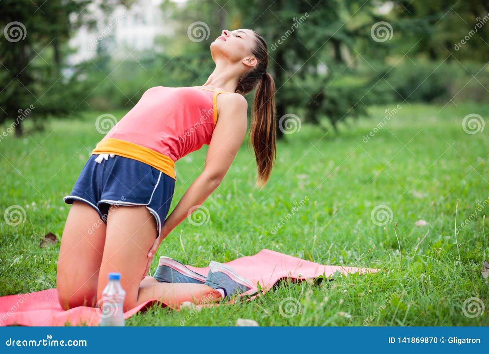 Geschikte jonge vrouw het praktizeren yoga in een stadspark, die Tibetaanse rite nummer drie doen
