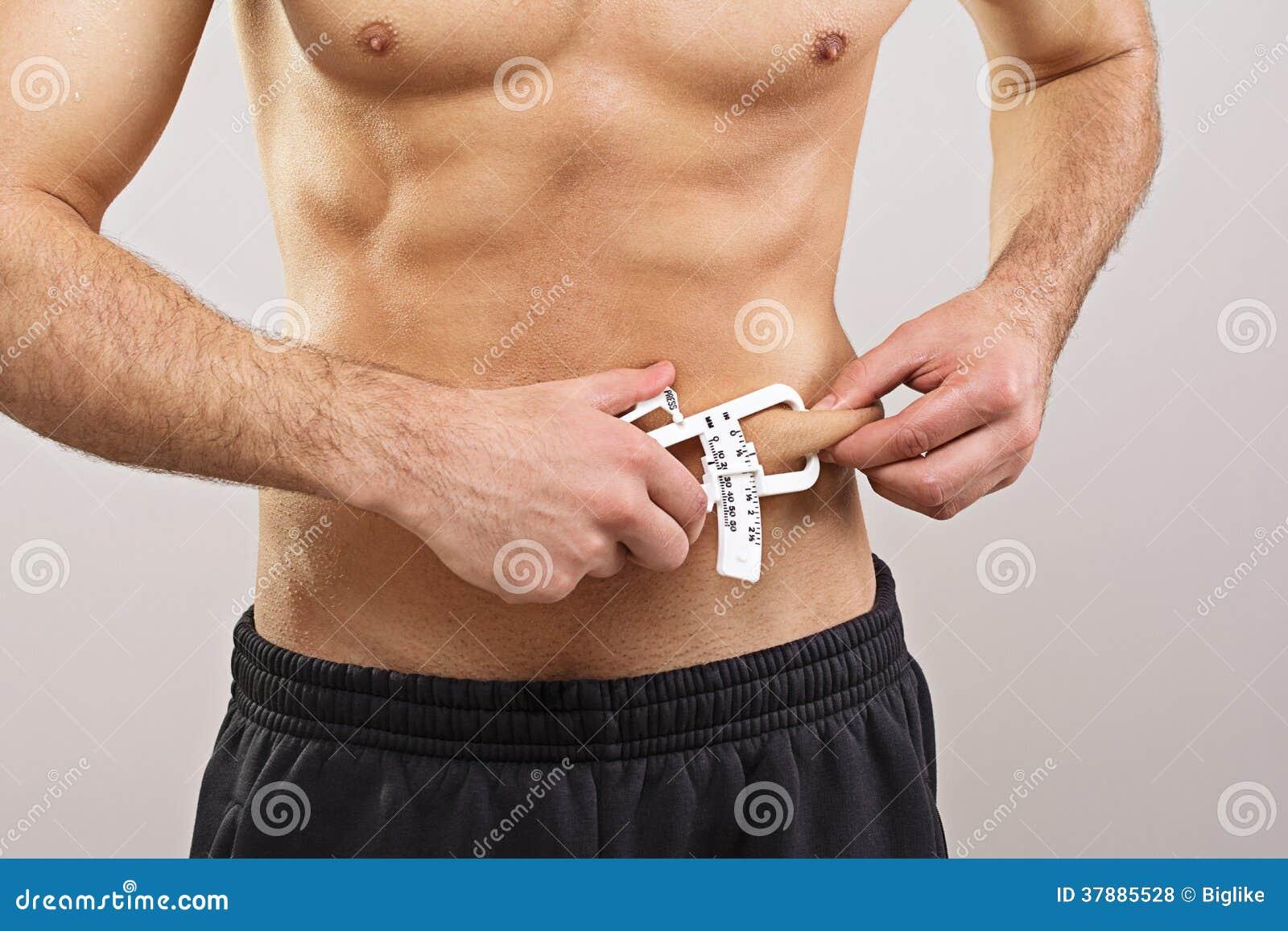 Geschikte sportman die lichaamsvet met beugel meten