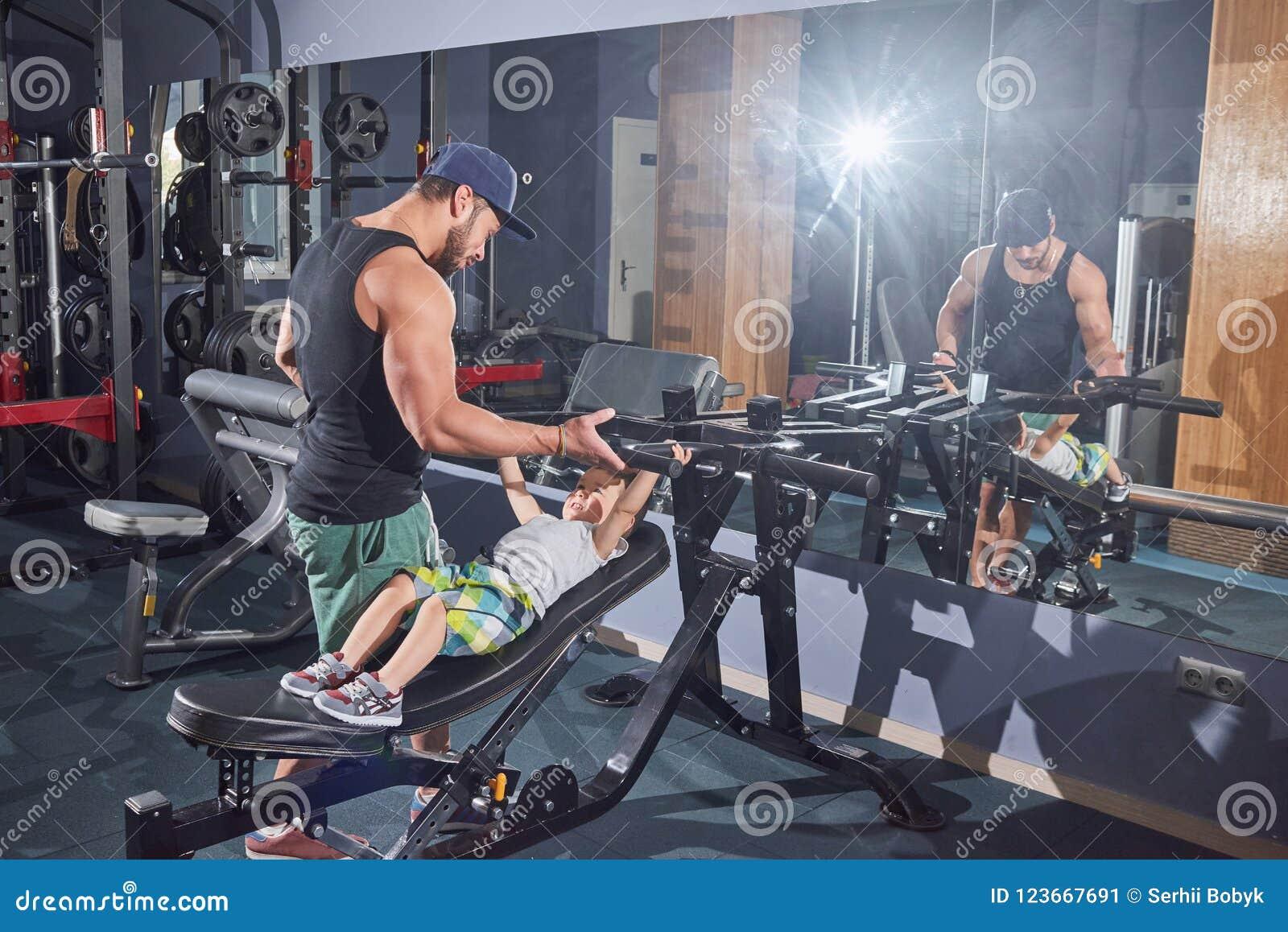 Geschikte vader die zijn kleine zoon helpen om op simulator op te leiden