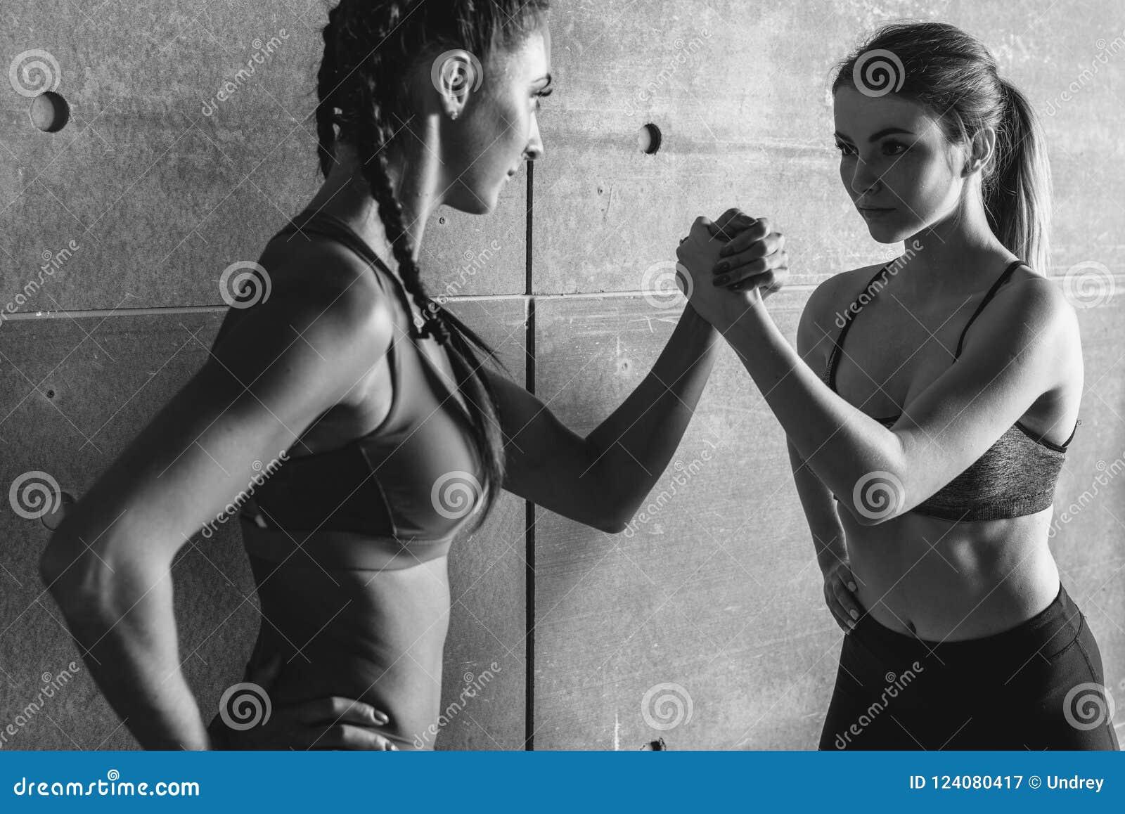 Geschikte vrouwen die handen met een vrouwelijke tegenstander houden die in haar ogen kijken