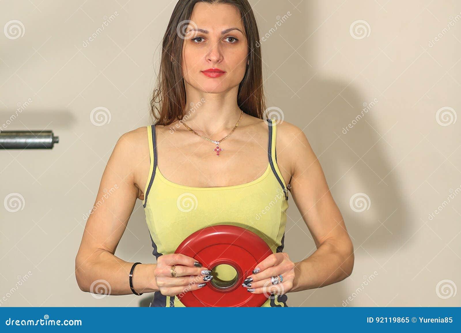 Geschiktheid en fysieke oefeningen Het jonge mooie witte meisje in een geel en grijs sportenkostuum leidt met een spruit van de b