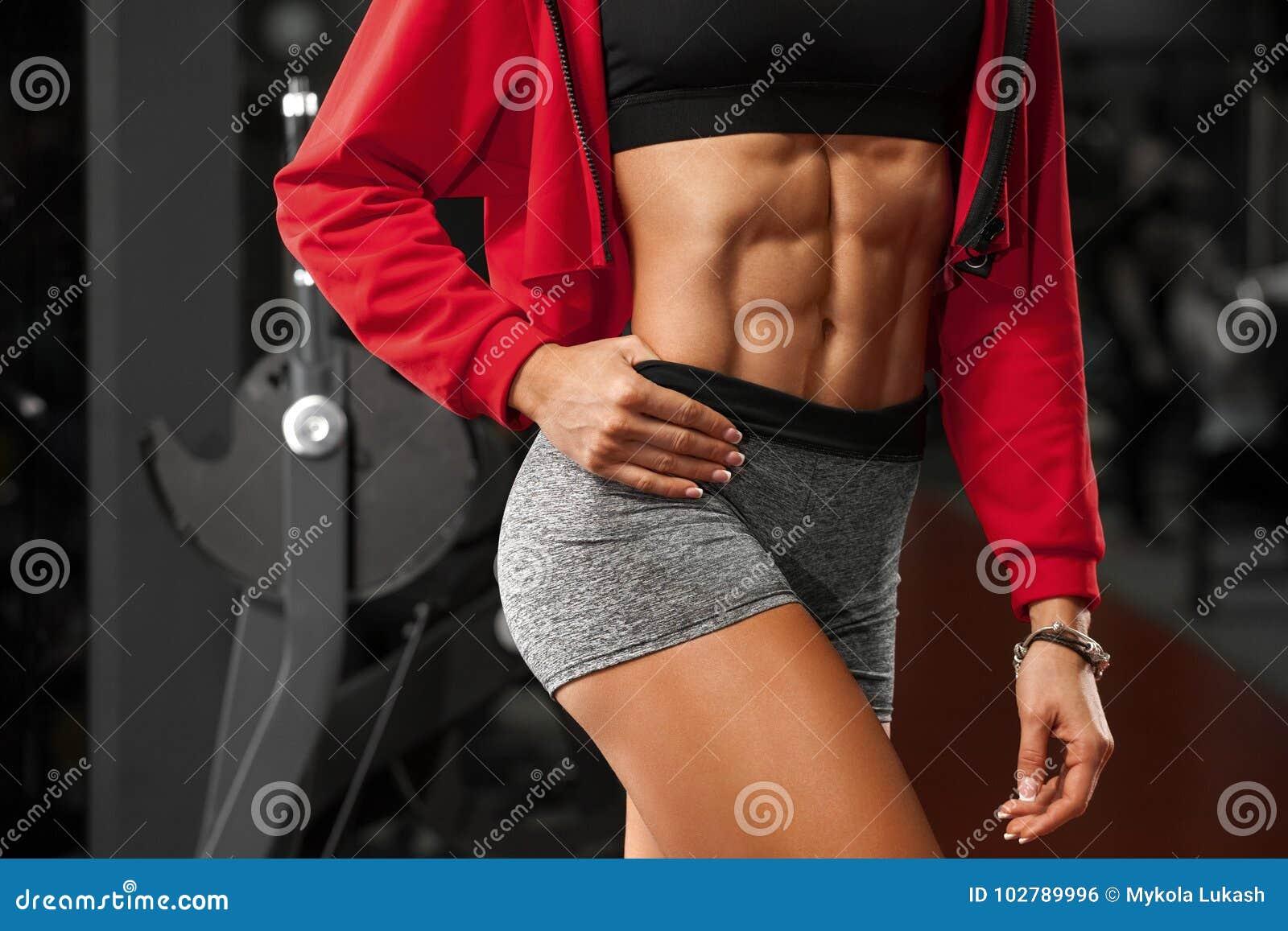 Geschiktheids sexy vrouw die abs en vlakke buik in gymnastiek tonen Mooi atletisch meisje, gestalte gegeven buik, slanke taille