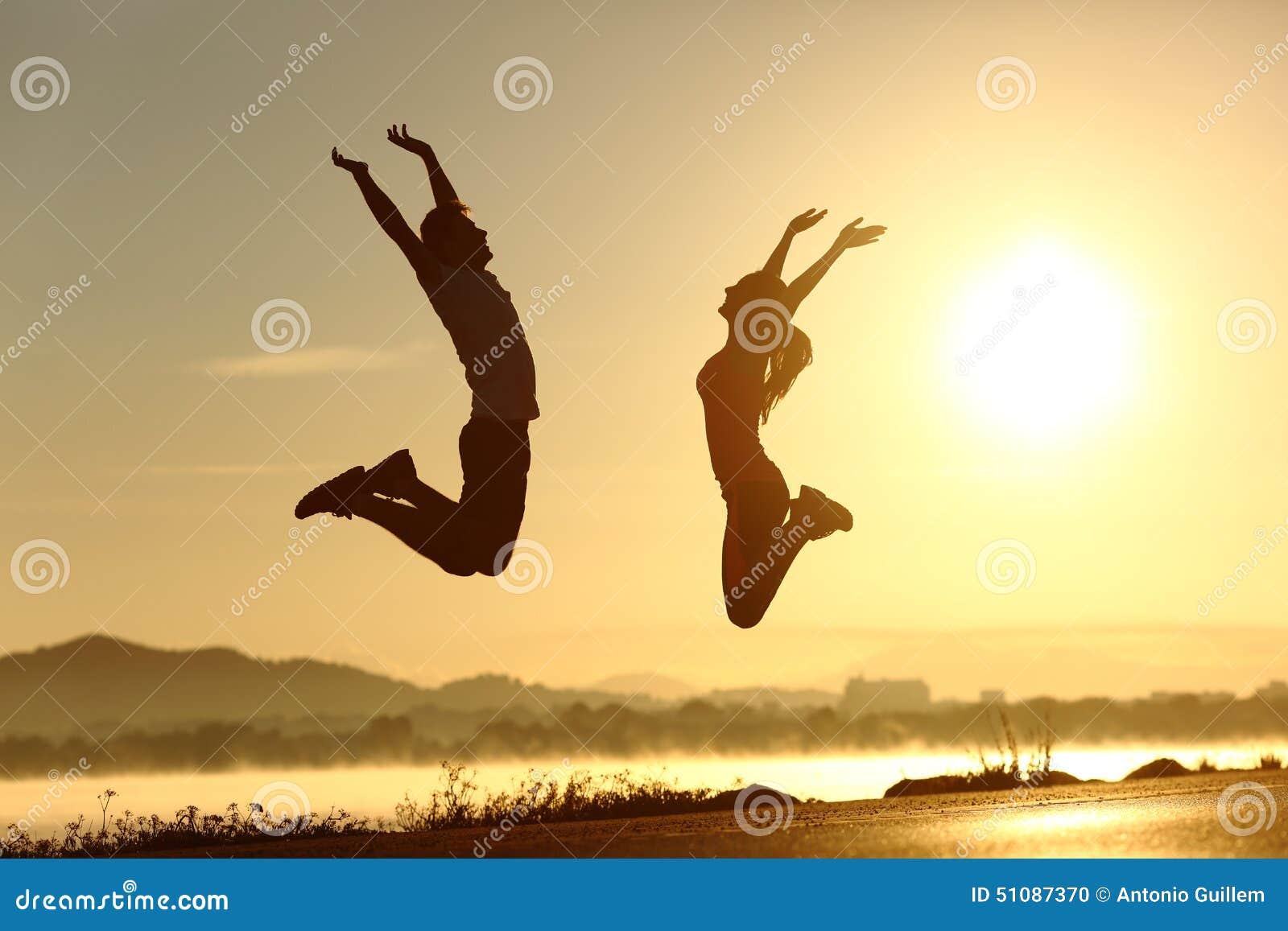 Geschiktheidspaar springen gelukkig bij zonsondergang