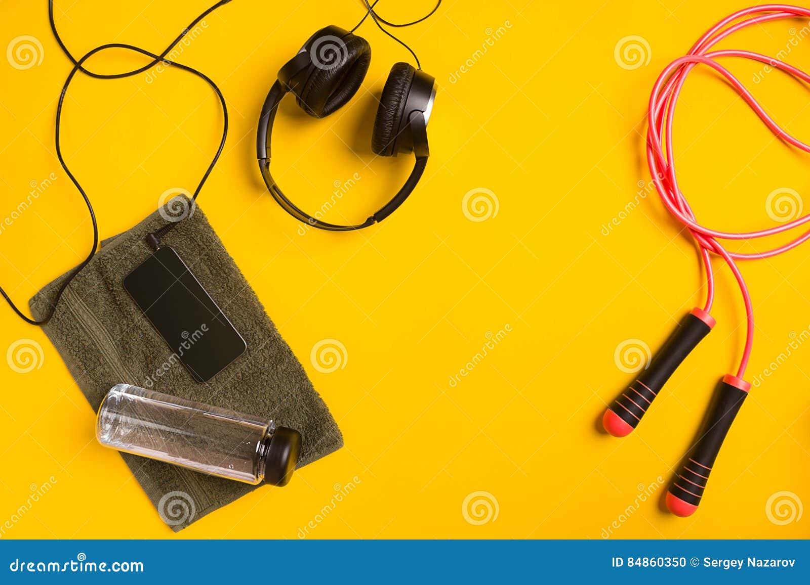 Geschiktheidstoebehoren op een gele achtergrond touwtjespringen, fles water, handdoek en hoofdtelefoons
