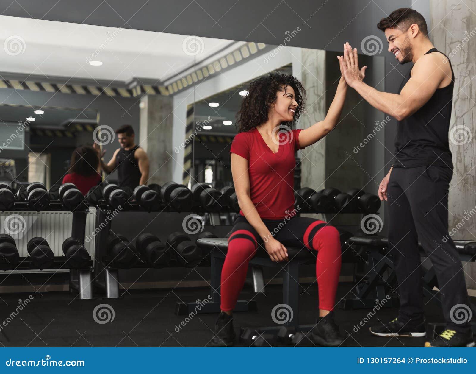 Geschiktheidstrainer en vrouw die elkaar hoogte vijf geven