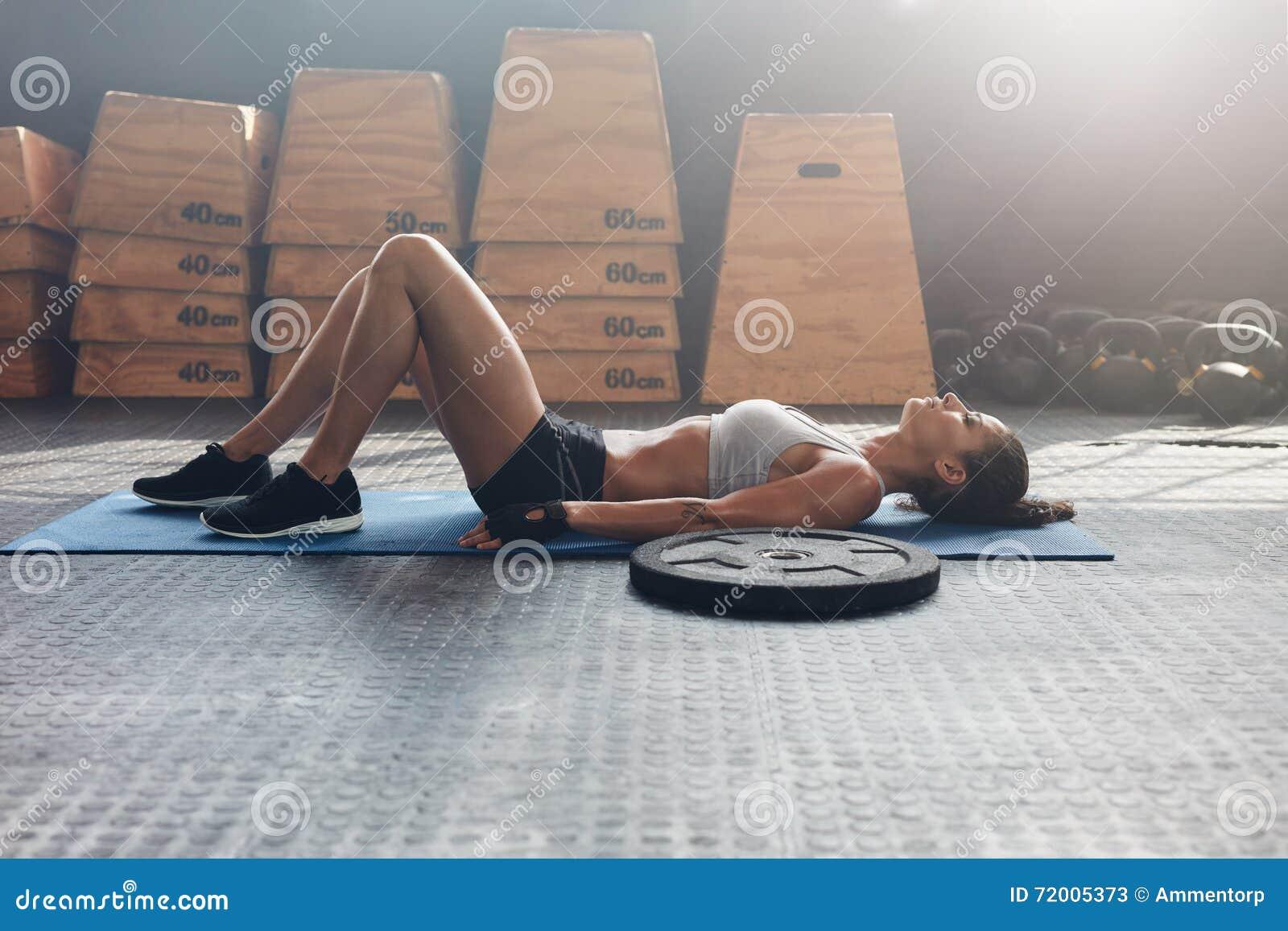 Geschiktheidsvrouw die op haar terug na een gymnastiektraining liggen