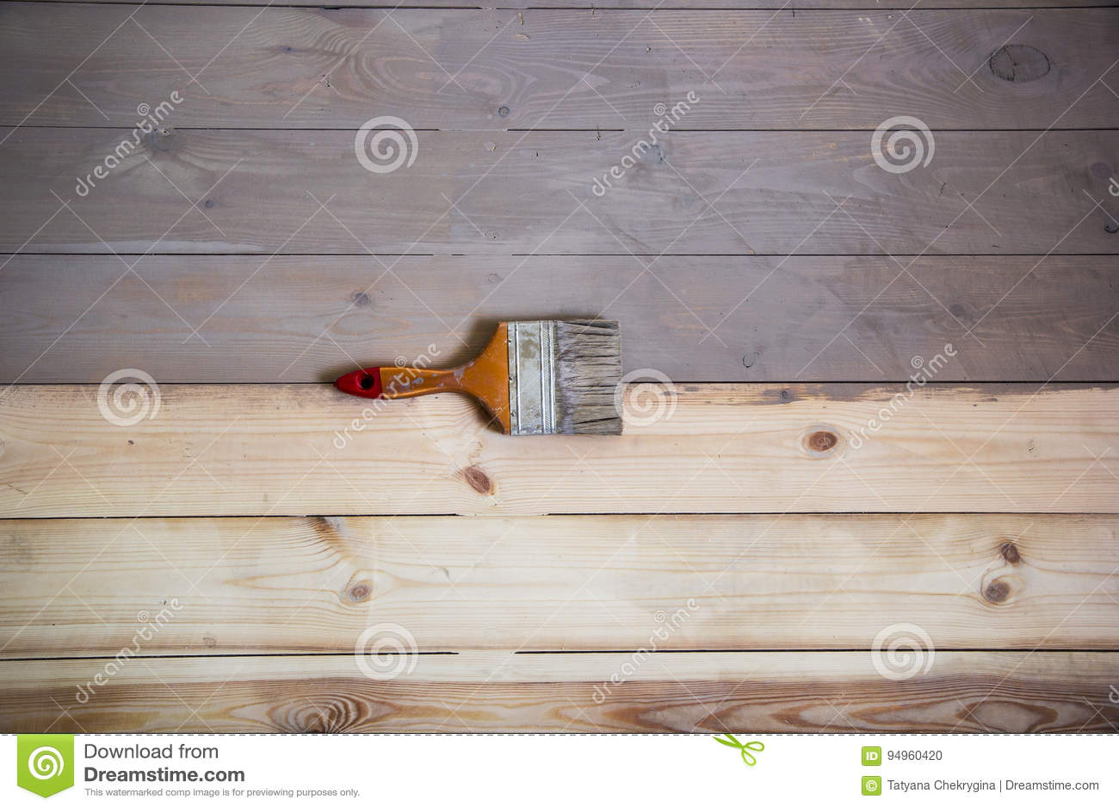 Geschilderde houten vloer met grijze kleur en een borstel op de