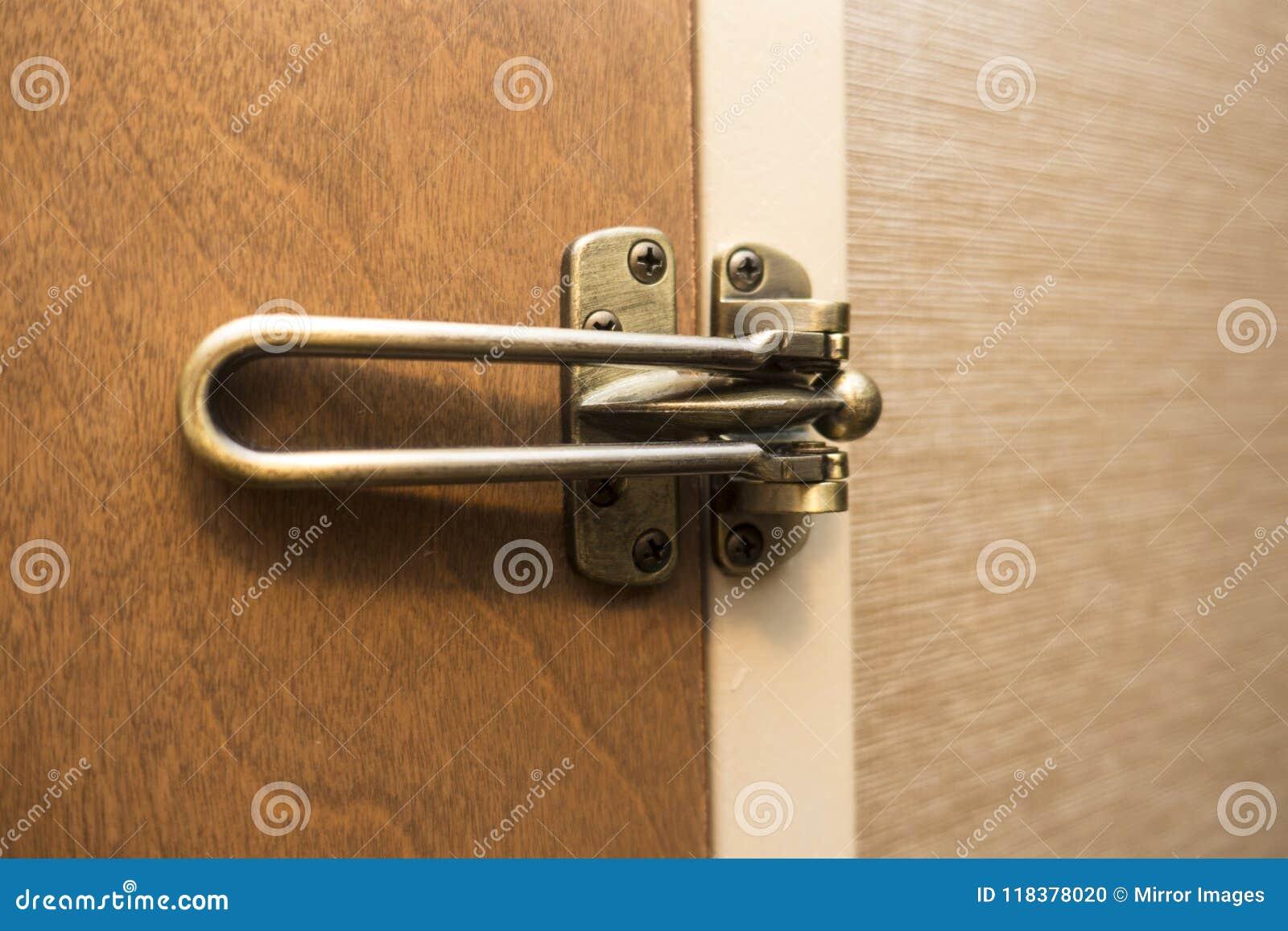 Geschlossene und verschlossene braune hölzerne Tür mit kupfernem Messing färbte Klinke