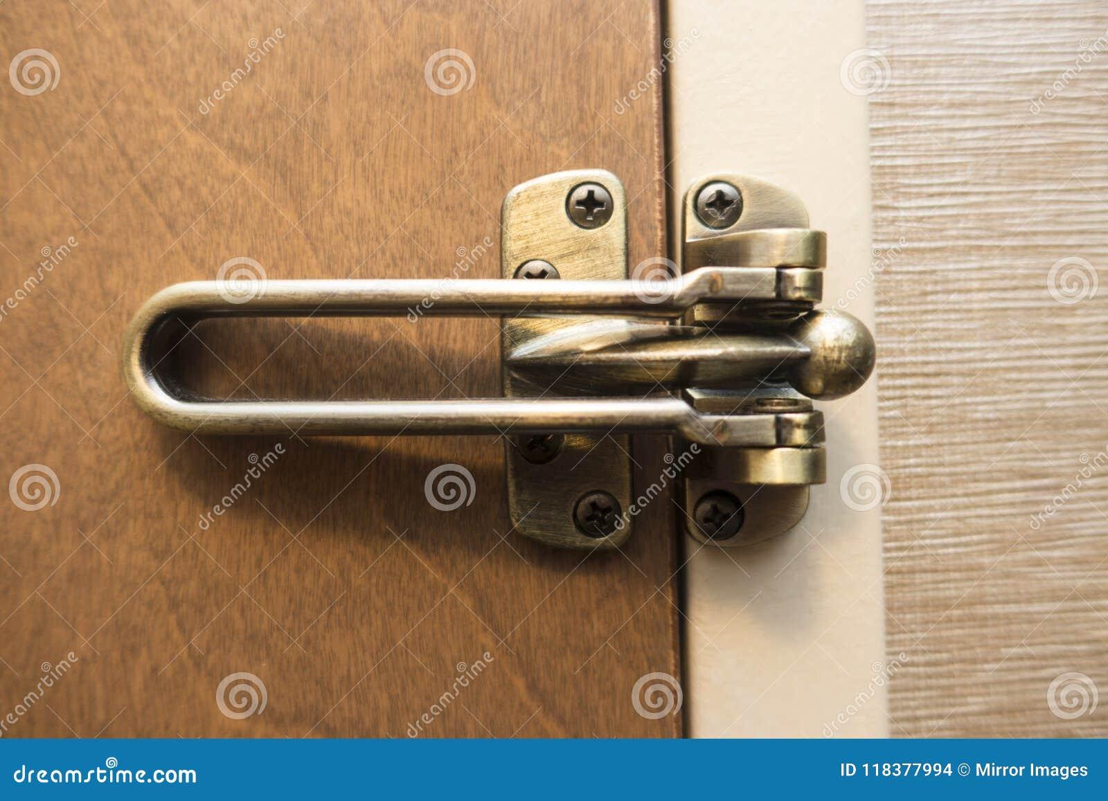 Geschlossene und verschlossene braune hölzerne Tür mit kupfernem Messing färbte latc