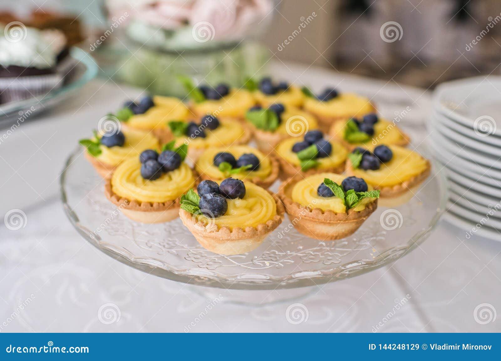 Geschmackvolle Tartlets mit Schlagsahne und Blaubeeren auf Tabelle im Restaurant