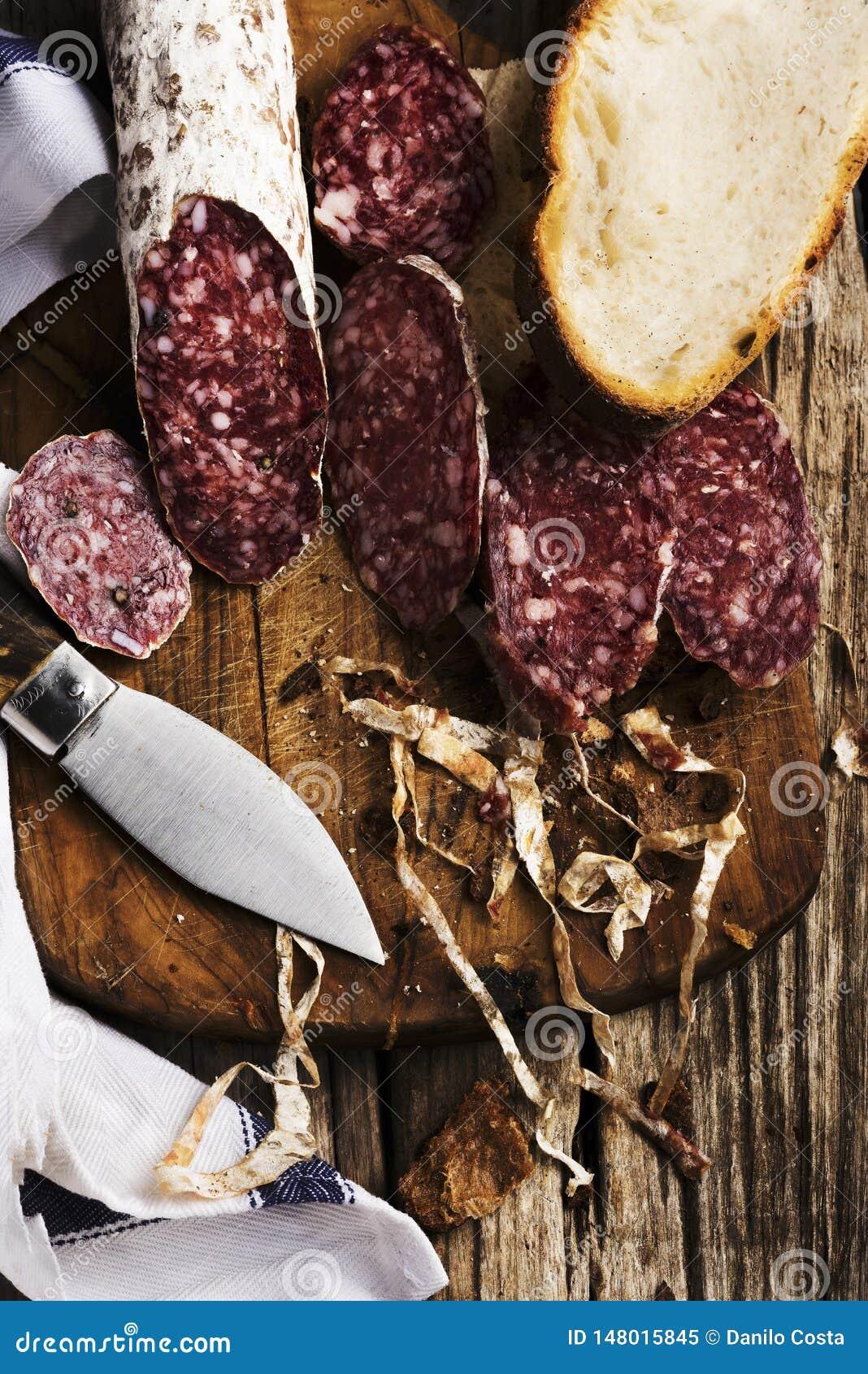 Geschnittene †‹â€ ‹Salami auf hölzernem Schneidebrett mit Messer