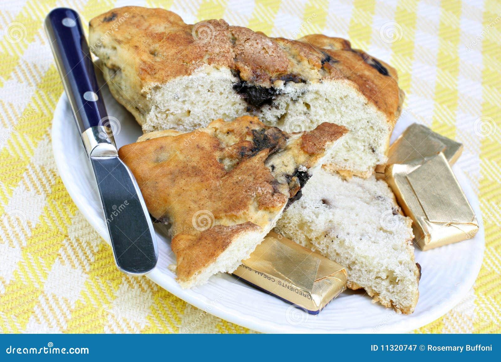 Geschnittener Blaubeere-Scone mit Butter auf der Seite.