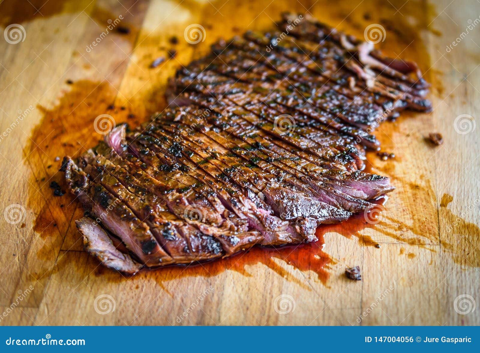 Geschnittener gegrillter saftiger marinierter Rindfleischbauchlappen auf h?lzernem Brett