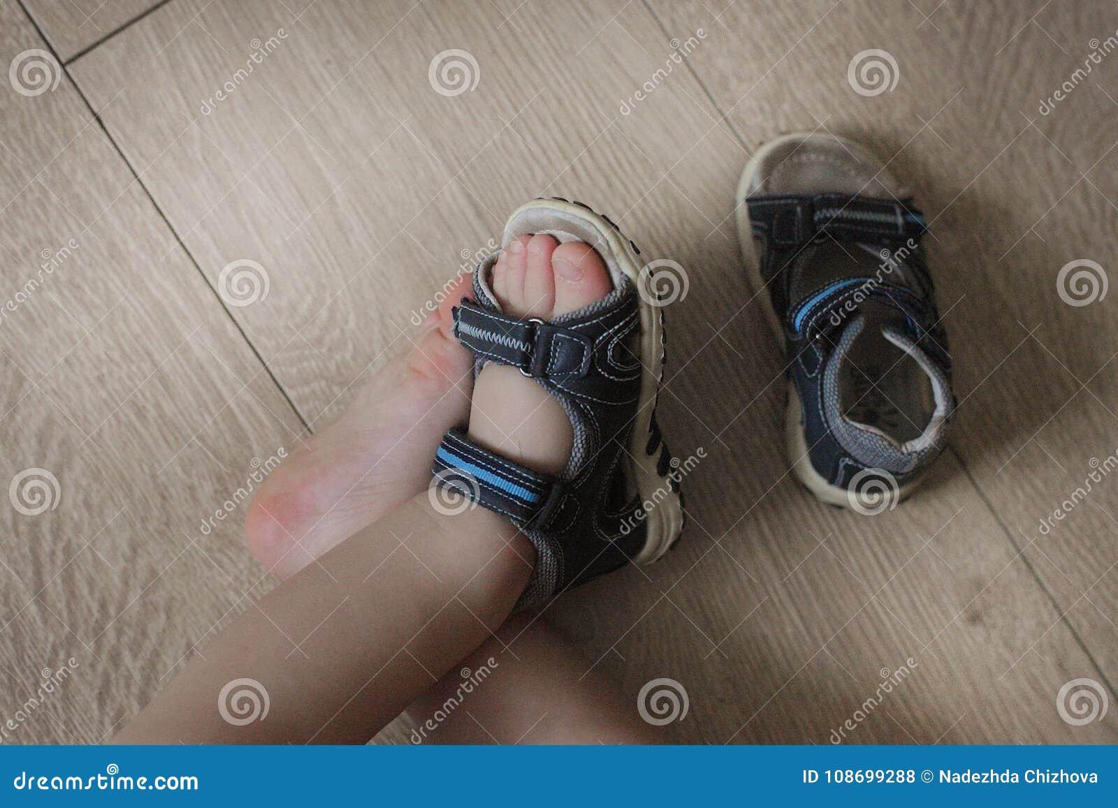 9c7814422d0 Geschoeide benen van de baby Kinderen` s sandals op hun voeten  Peuterschoenen Toeristensandals voor de